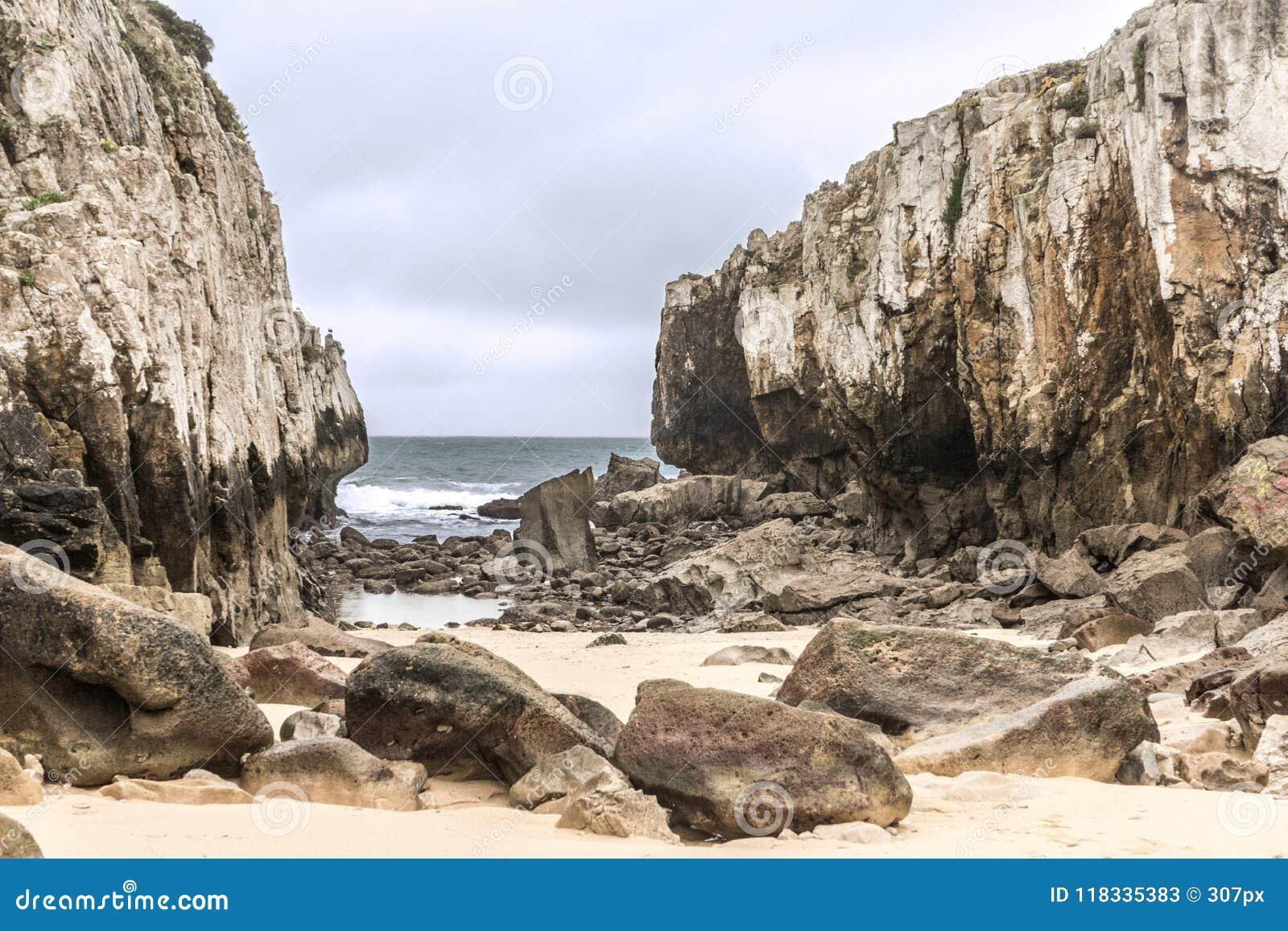 Praia escondida no meio de dois penhascos em um dia nebuloso