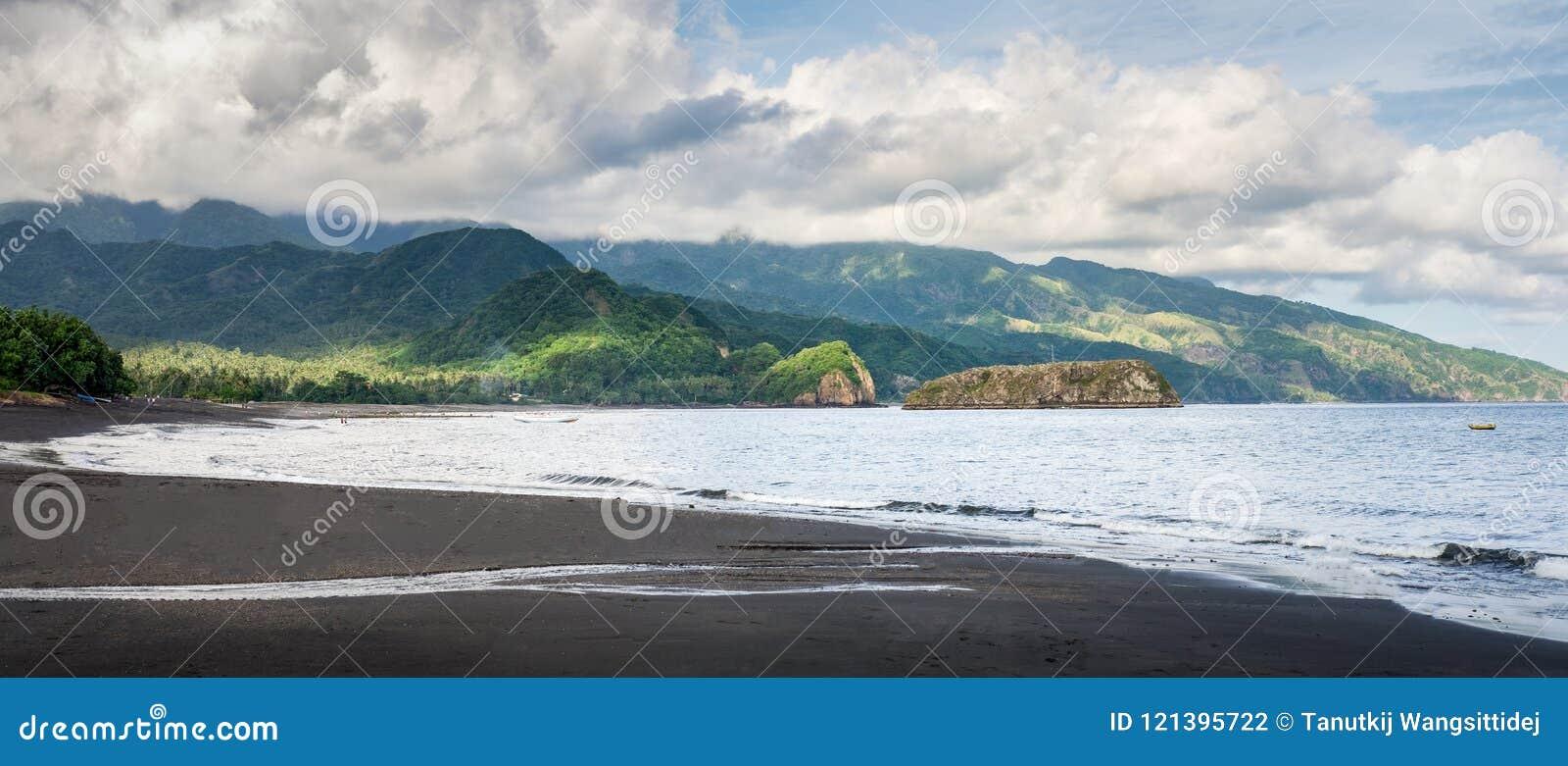 Praia preta da areia próximo pela cidade Ende A paisagem é notável com as montanhas, as nuvens e a luz no fundo, Ende, do leste
