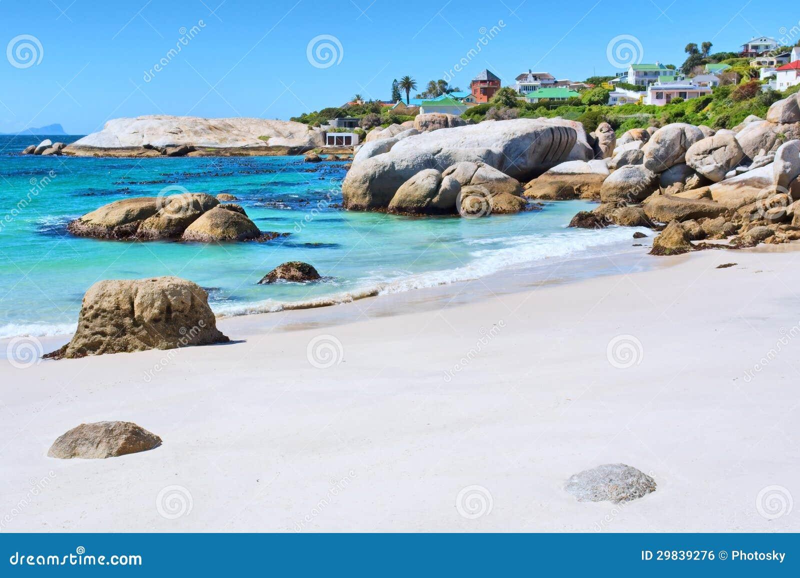 Praia rochosa na frente das casas