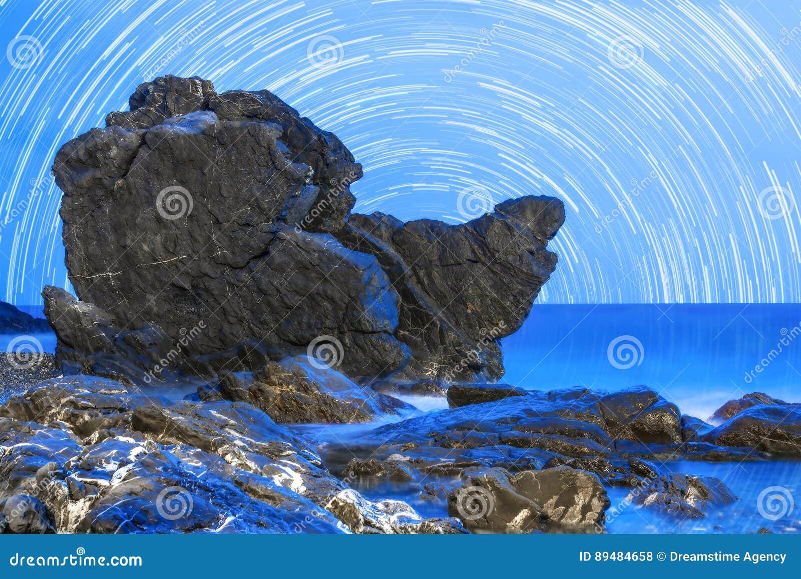 Praia rochosa na hora azul