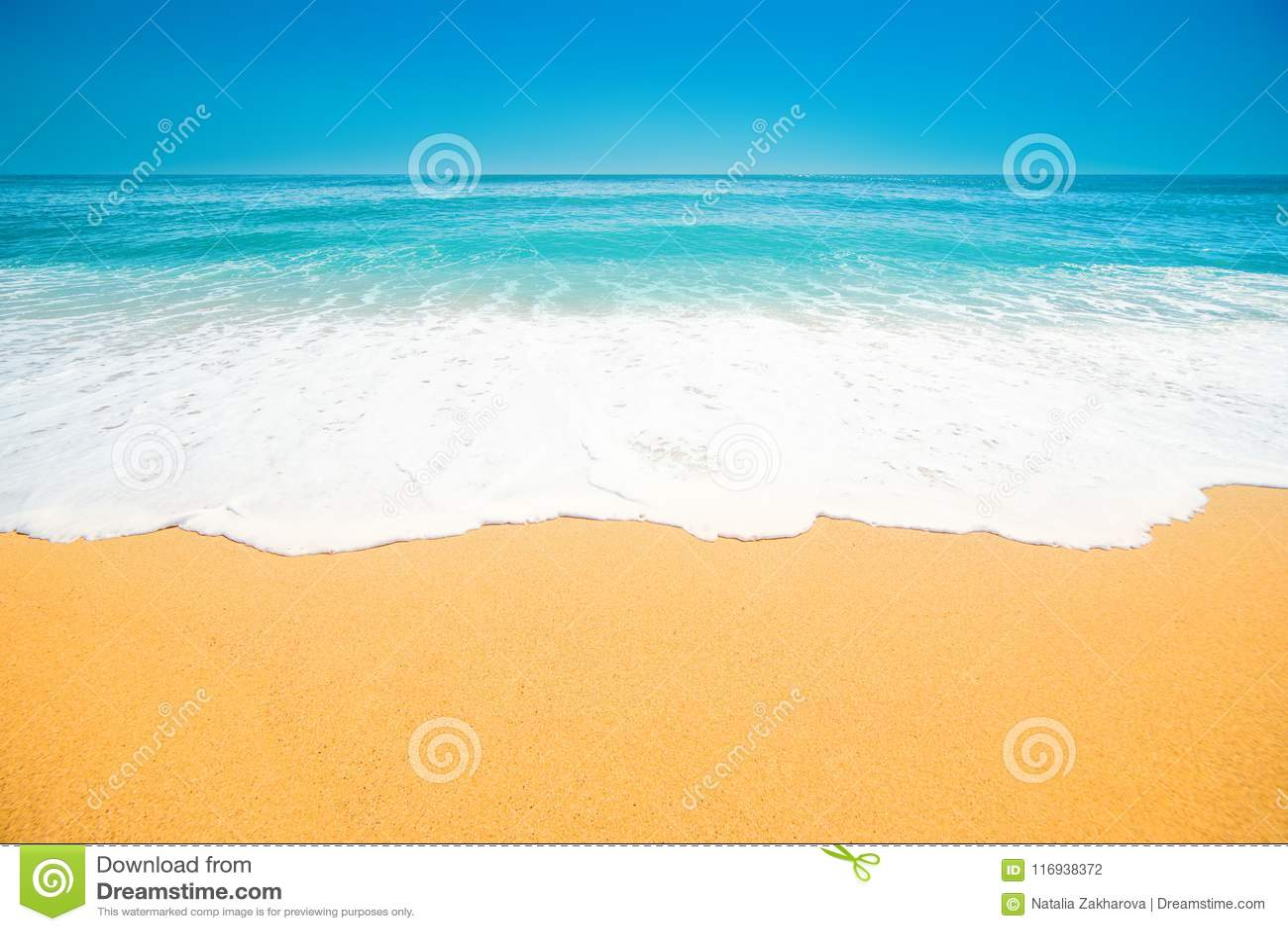 Praia tropical bonita com a onda macia do oceano azul, areia e