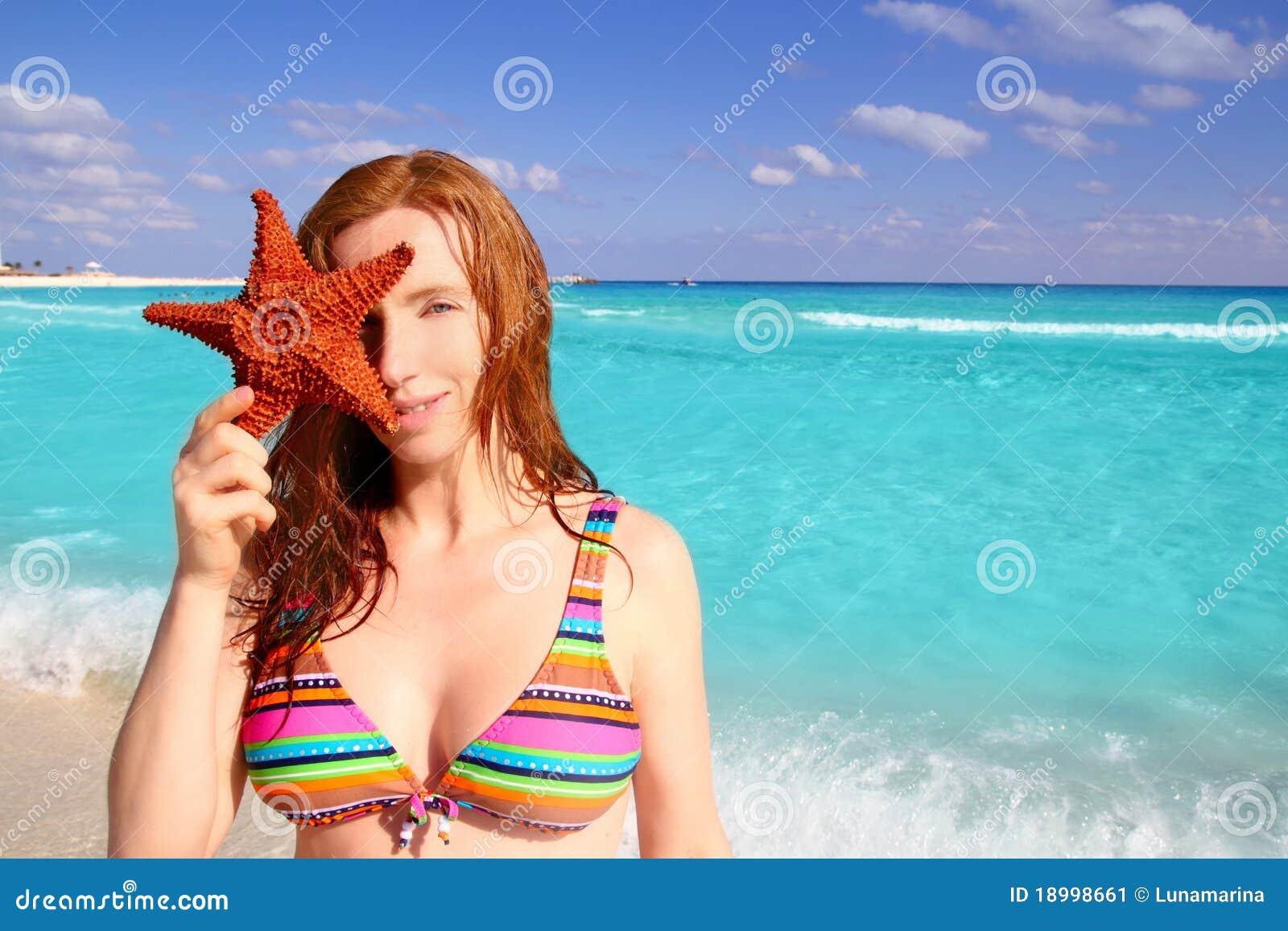 Praia tropical dos starfish da preensão da mulher do turista