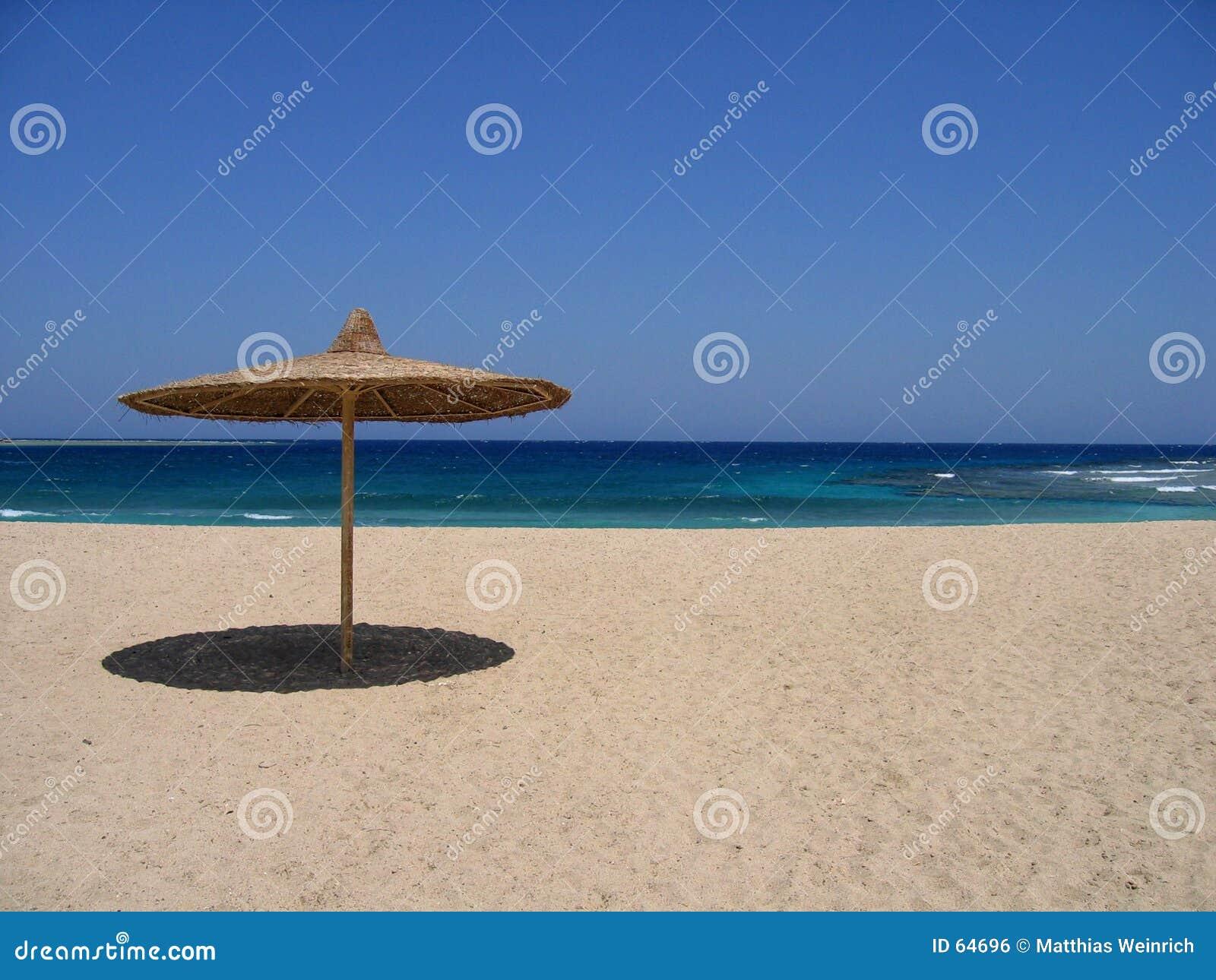 Praia vazia com pára-sol