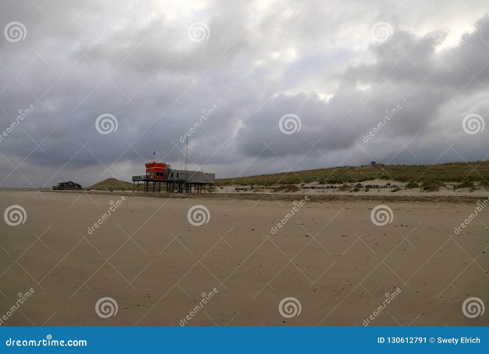 Praia vazia em um dia nebuloso na cidade pequena litoral quieta, os Países Baixos