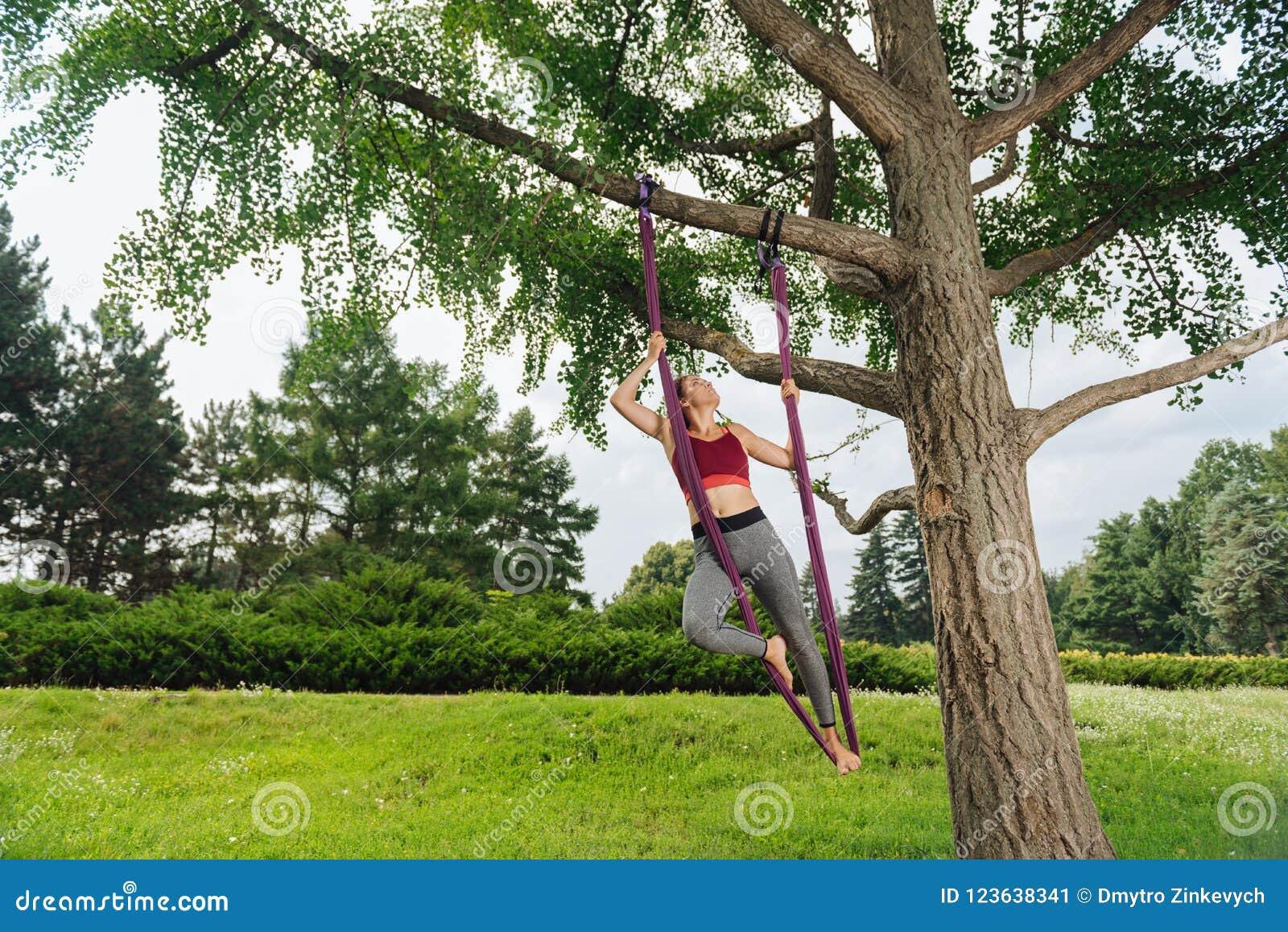 Praktiserande klipsk yoga för idrotts- kvinna genom att använda trädet på ny luft