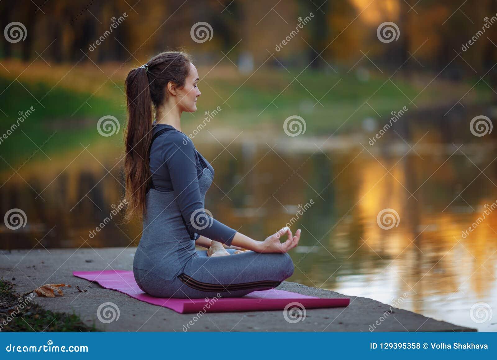 Praktiserande yoga för ung kvinna utomhus Kvinnlign mediterar utomhus- i framdel av den härliga höstnaturen