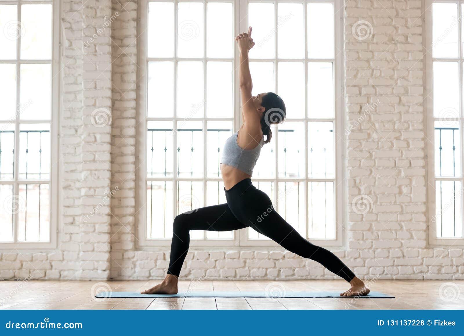 Praktiserande yoga för ung sportig attraktiv kvinna som gör krigare en