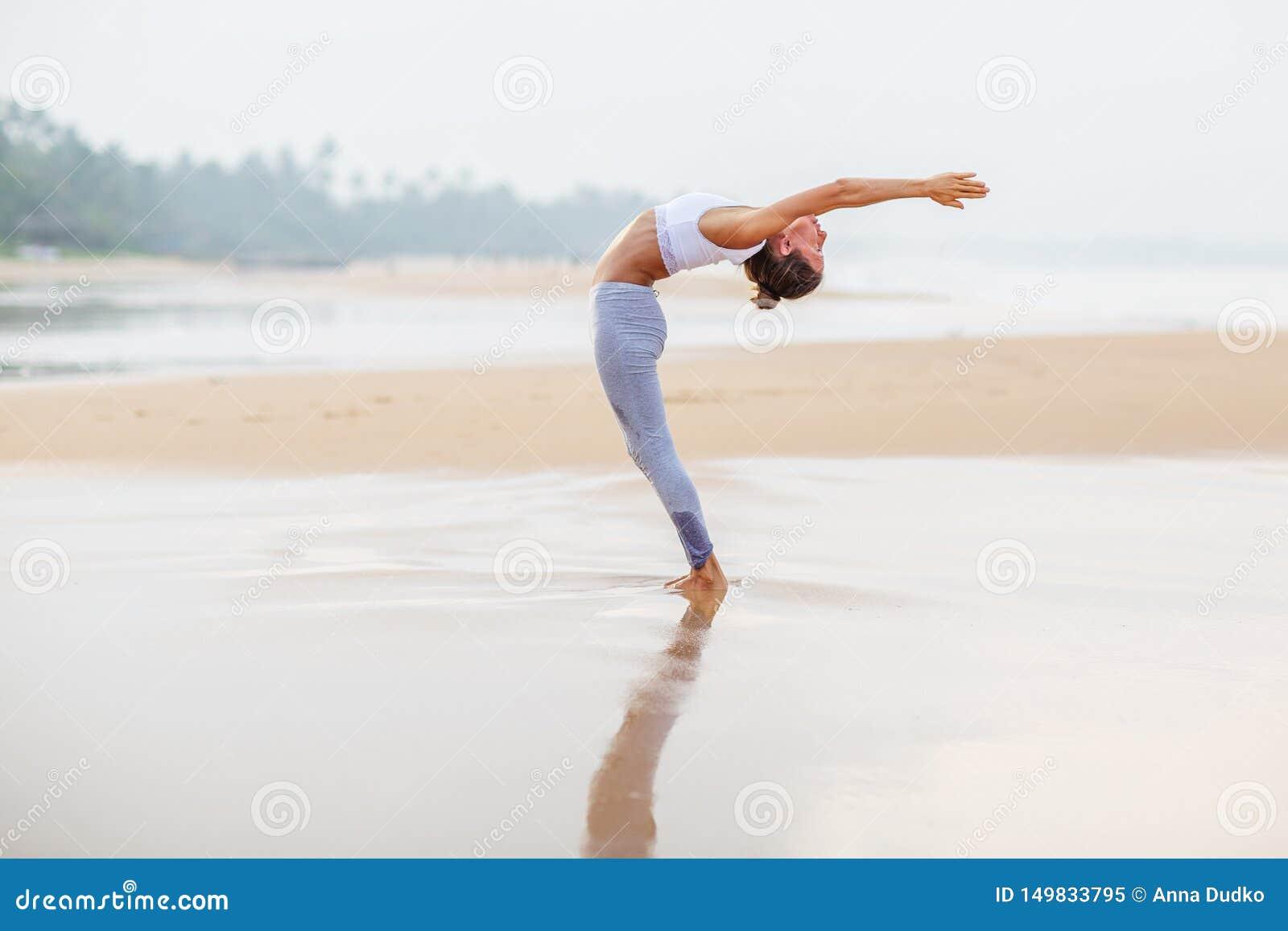Praktiserande yoga f?r Caucasian kvinna p? kusten av v?ndkretshavet