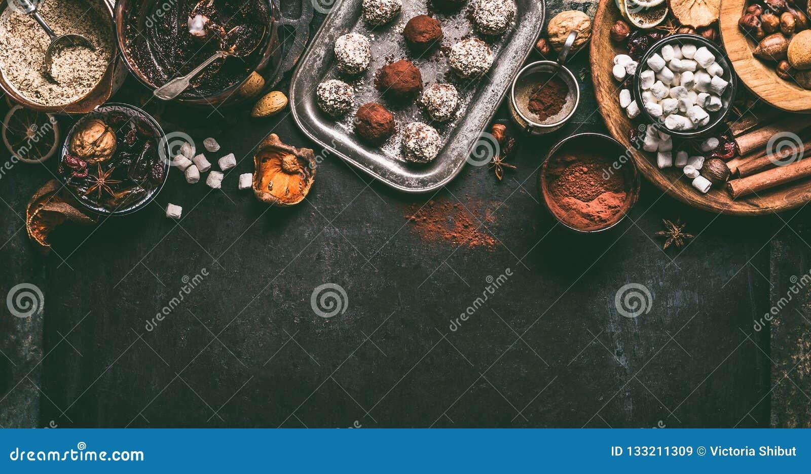 Praline casalinghe del tartufo di cioccolato del vegano con i frutti secchi ed ingredienti matti della miscela su fondo scuro, vi