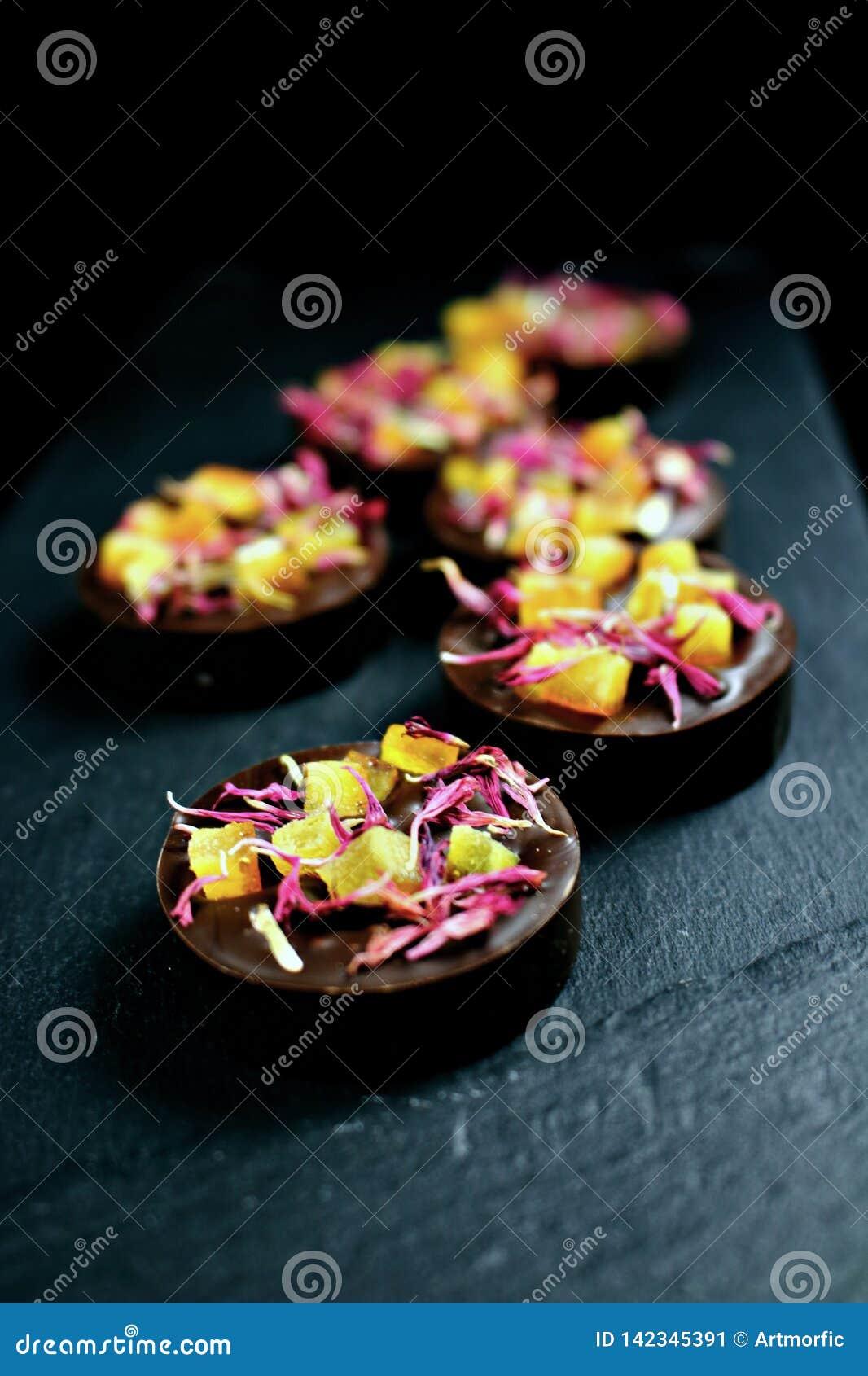 Praline mistiche del cioccolato fondente con i petali arancio e rossi canditi della centaurea su fondo scuro
