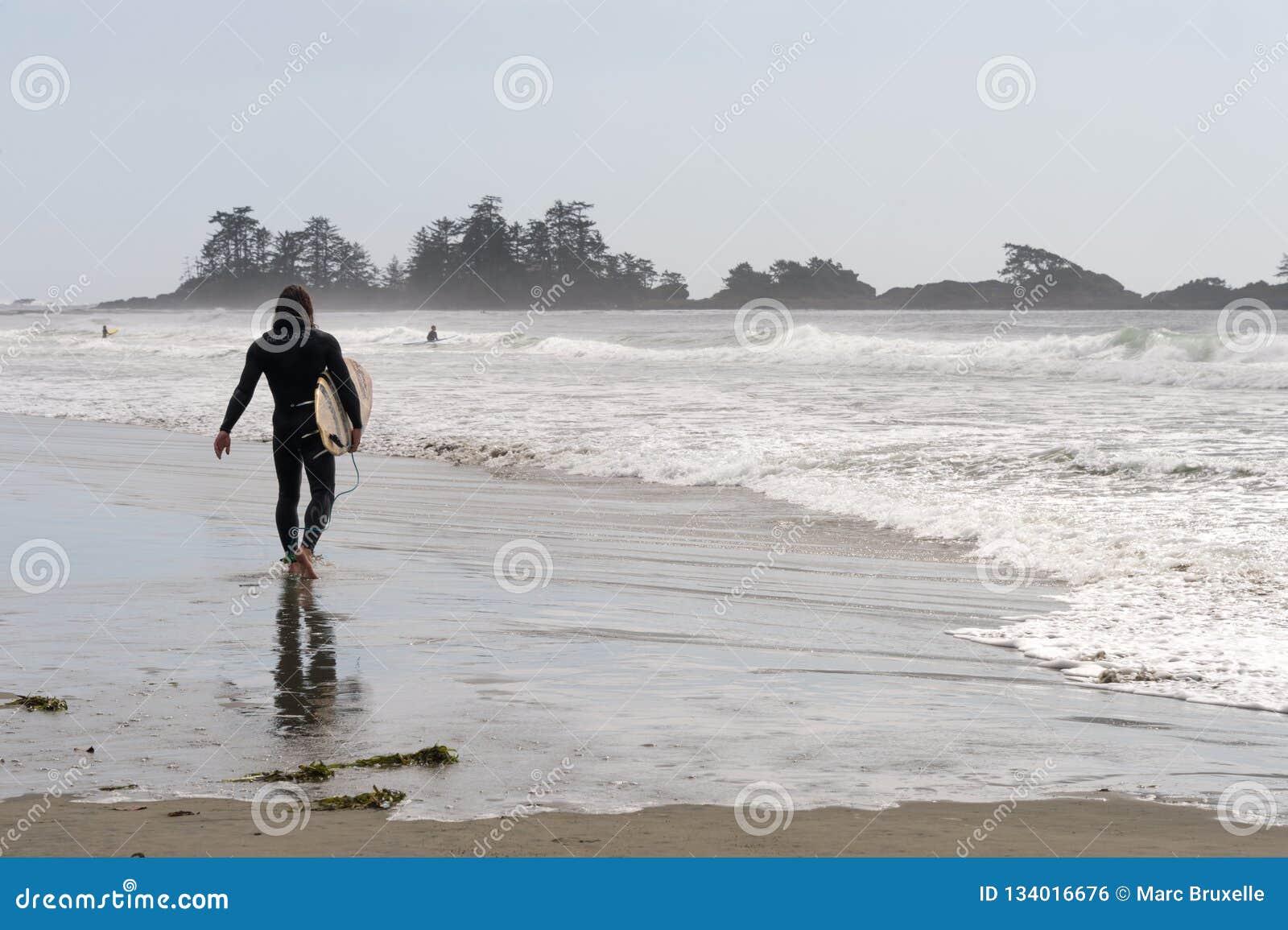 Prancha da terra arrendada do surfista em Canadá