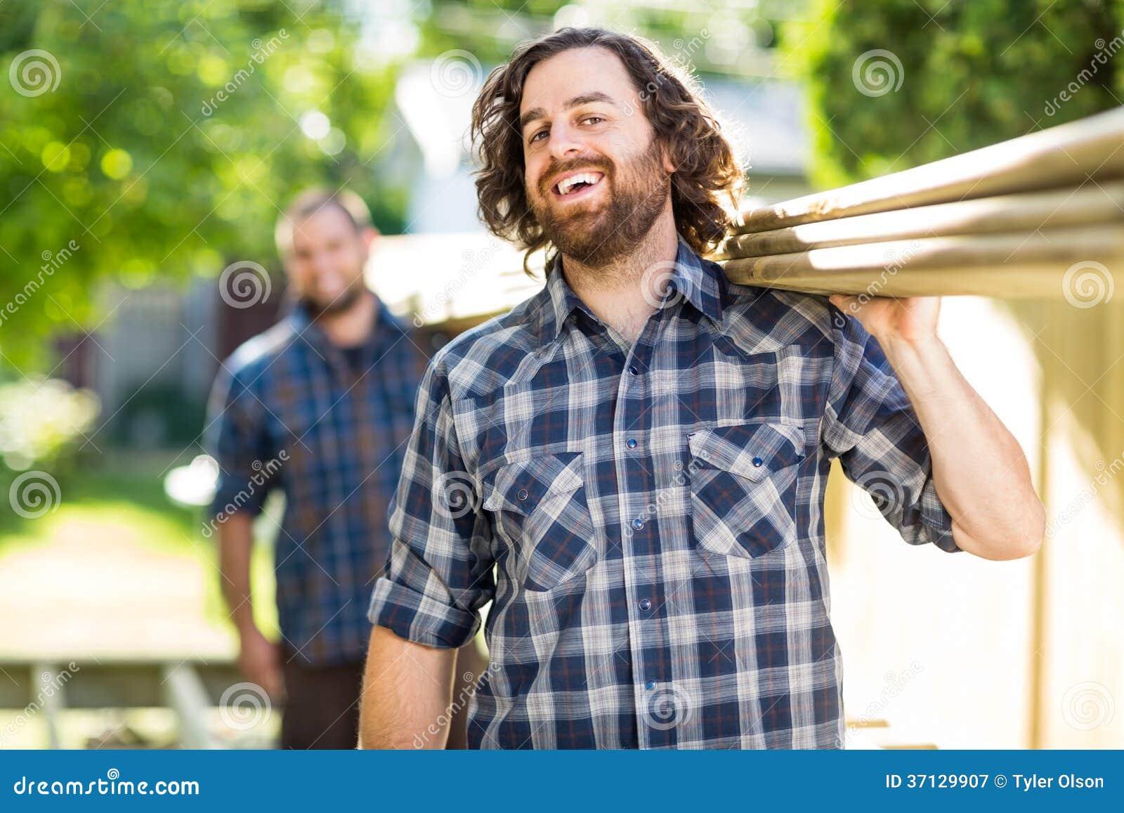 Pranchas de With Coworker Carrying do carpinteiro quando
