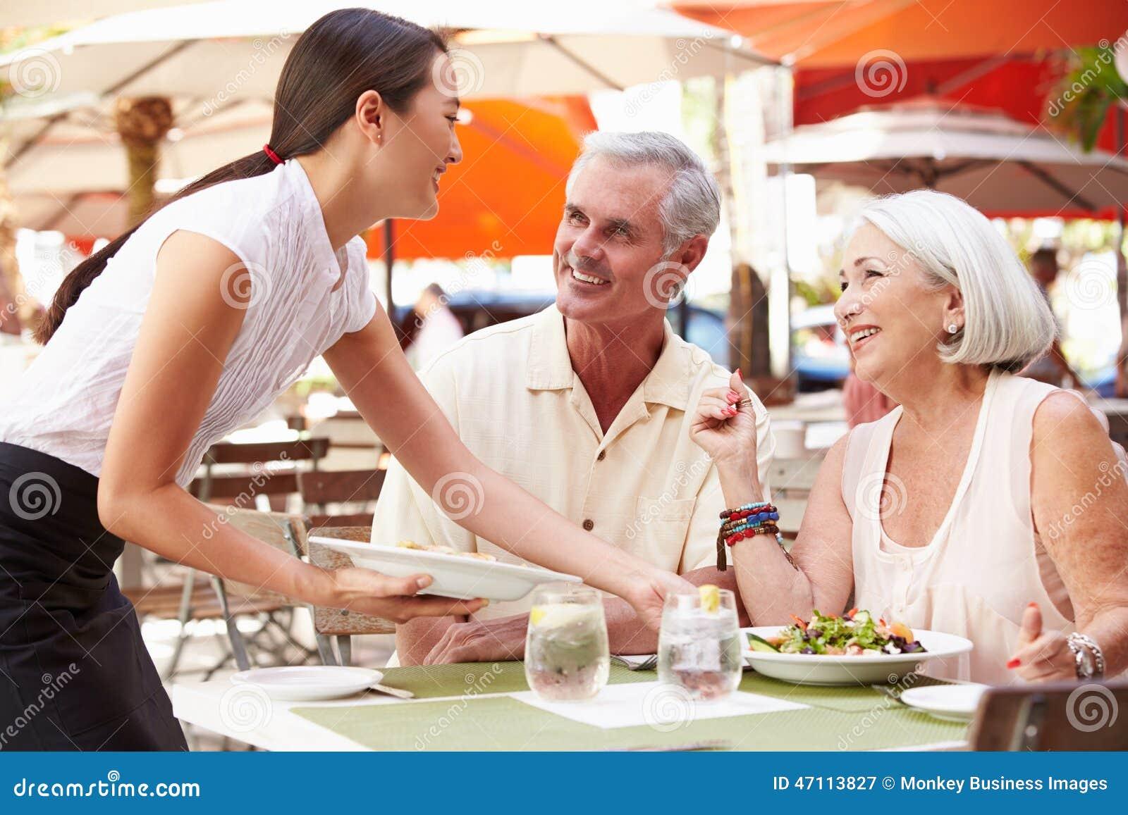 Pranzo di Serving Senior Couple della cameriera di bar in ristorante all aperto