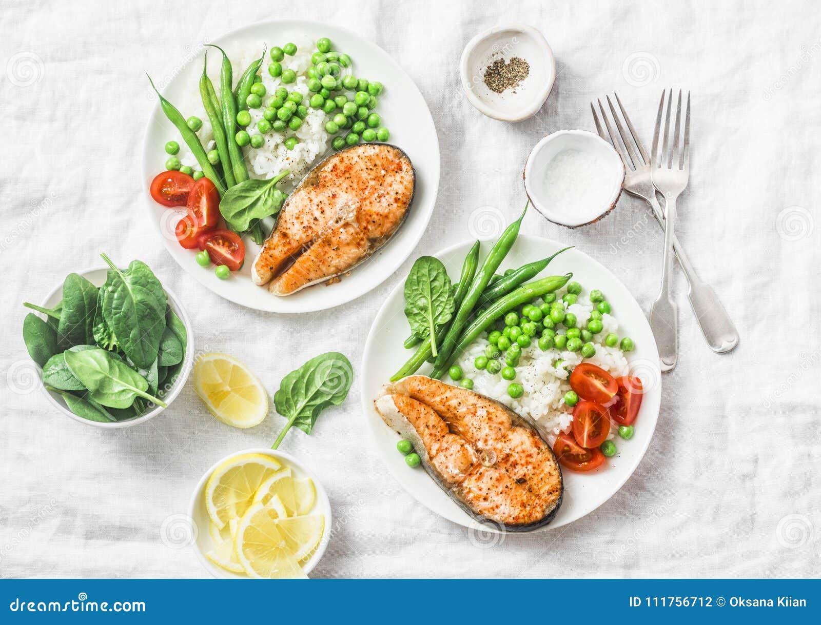 Pranzo mediterraneo equilibrato sano di dieta - salmone al forno, riso, piselli e fagiolini su un fondo leggero, vista superiore