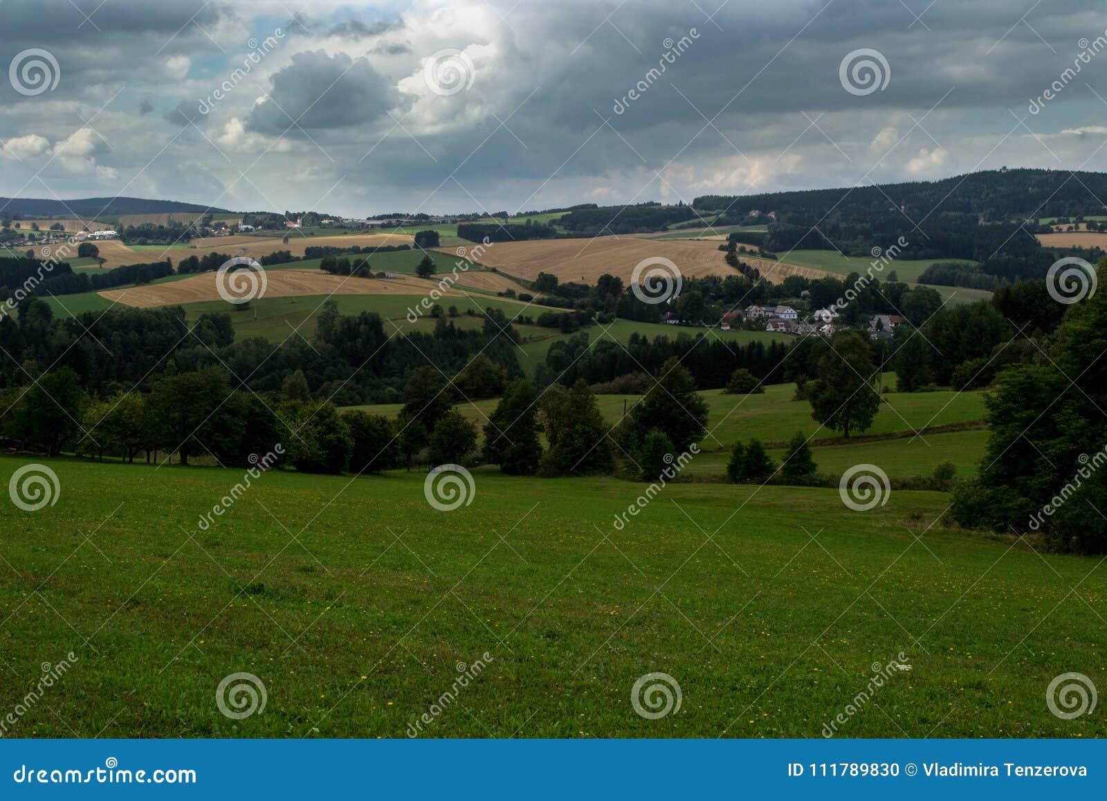 Prati verdi, campi gialli e foreste sotto le nuvole di tempesta
