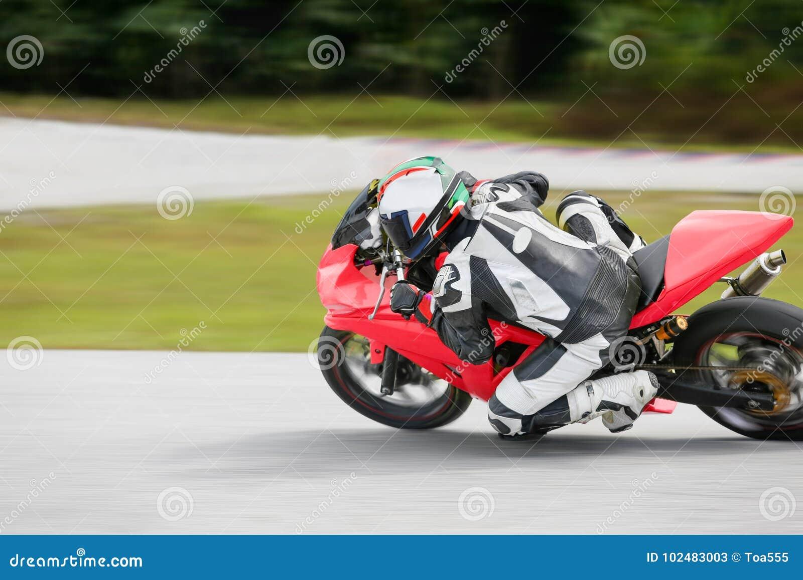 Pratique en matière de moto se penchant dans un coin rapide sur la voie
