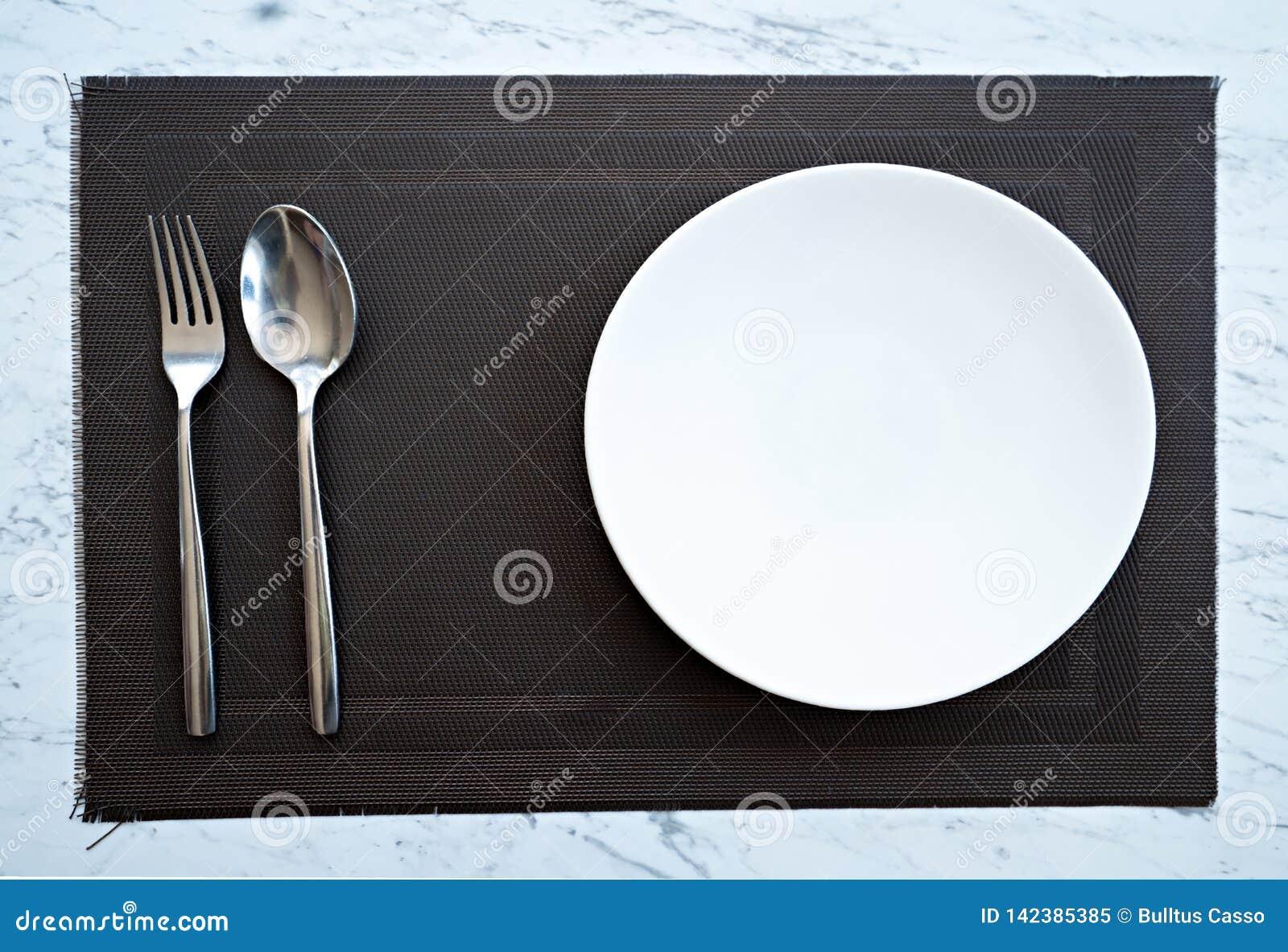 Prato com uma colher e forquilha na tabela