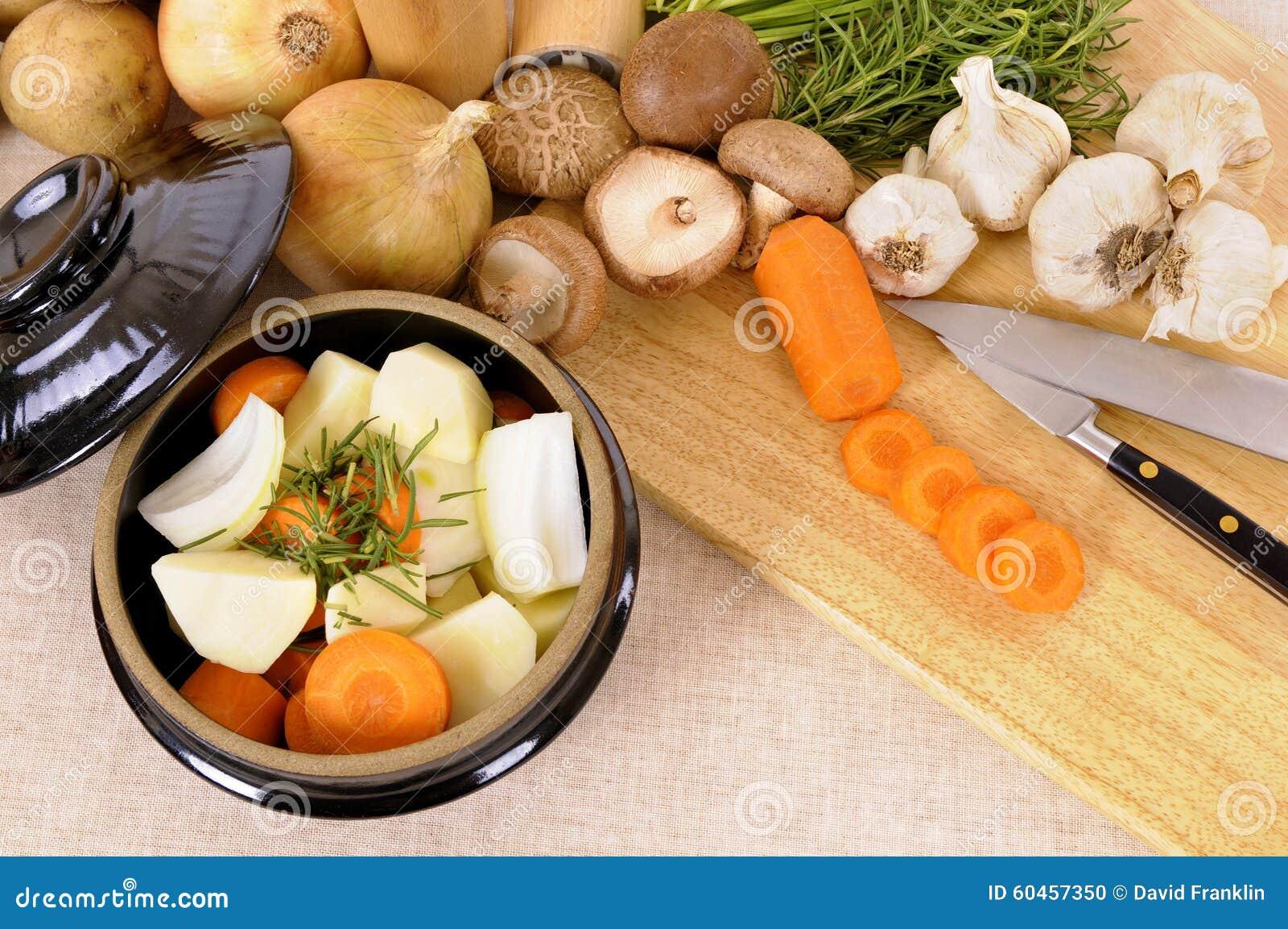 Prato da caçarola com vegetais e as ervas orgânicos na toalha de mesa de linho, placa de desbastamento de madeira