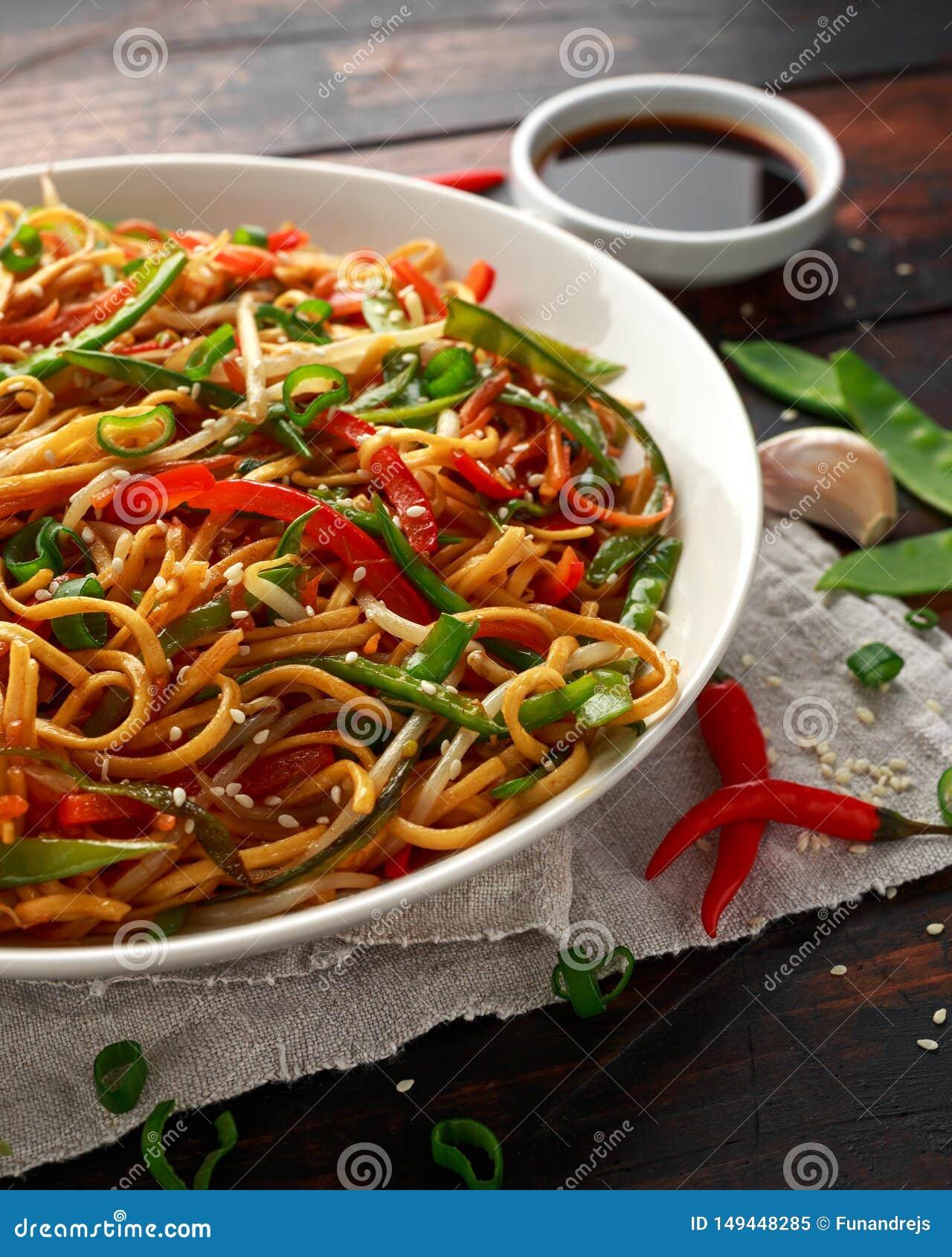 Prato do mein, dos macarronetes e dos vegetais da comida com hashis de madeira