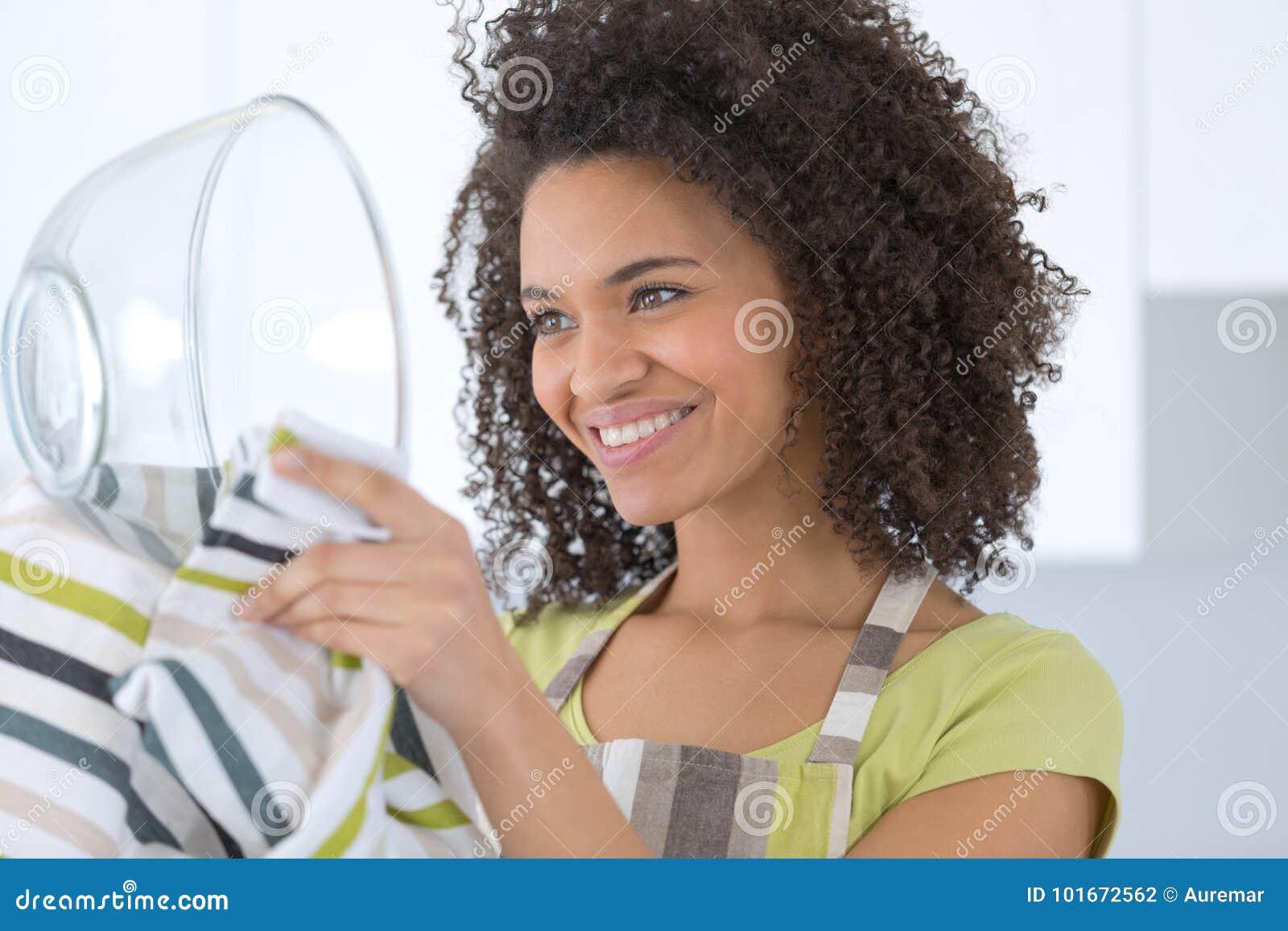 Pratos de lavagem da dona de casa nova bonita com esponja