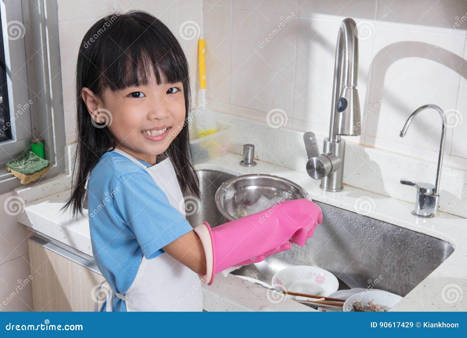 Pratos de lavagem da menina chinesa asiática na cozinha