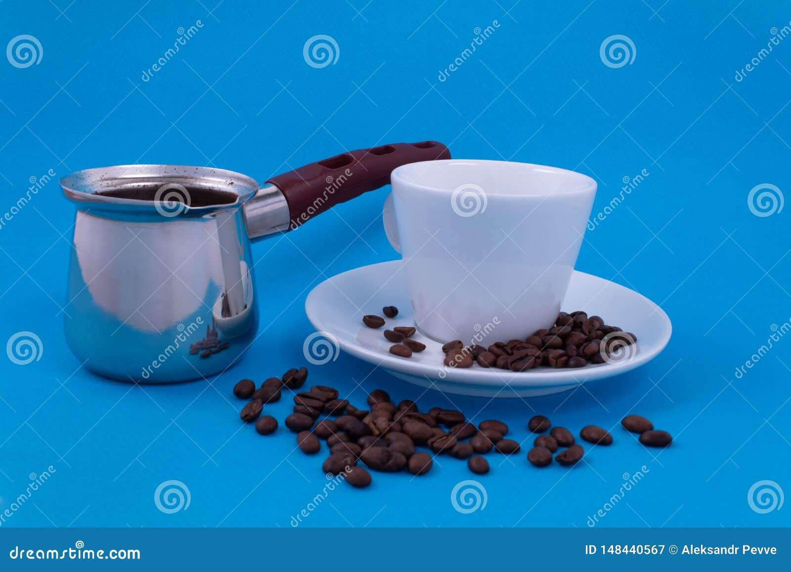 Pratos do metal com café fabricado cerveja ao lado de uma posição branca do copo da porcelana em uns pires