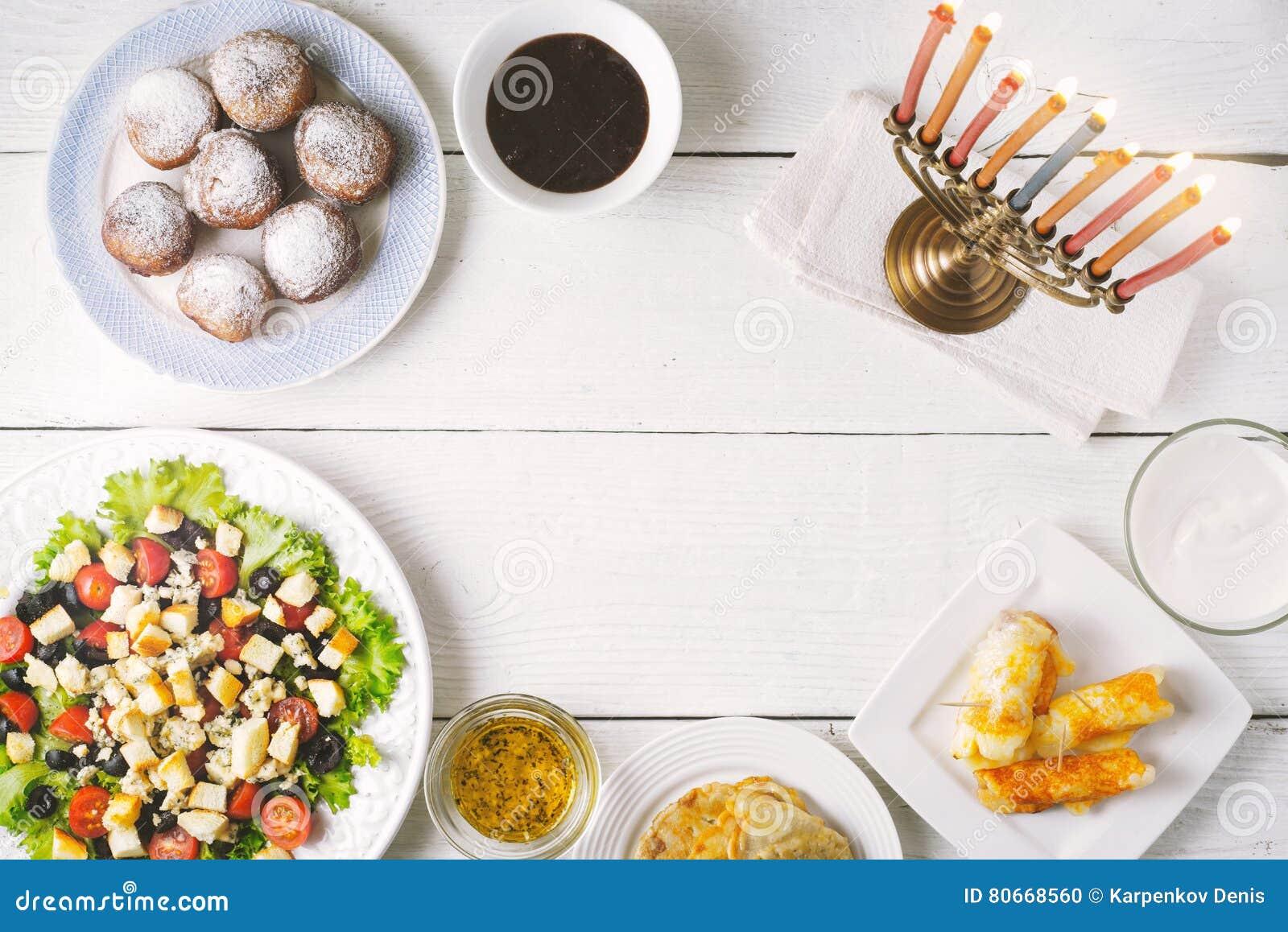 Pratos tradicionais do Hanukkah na tabela de madeira branca