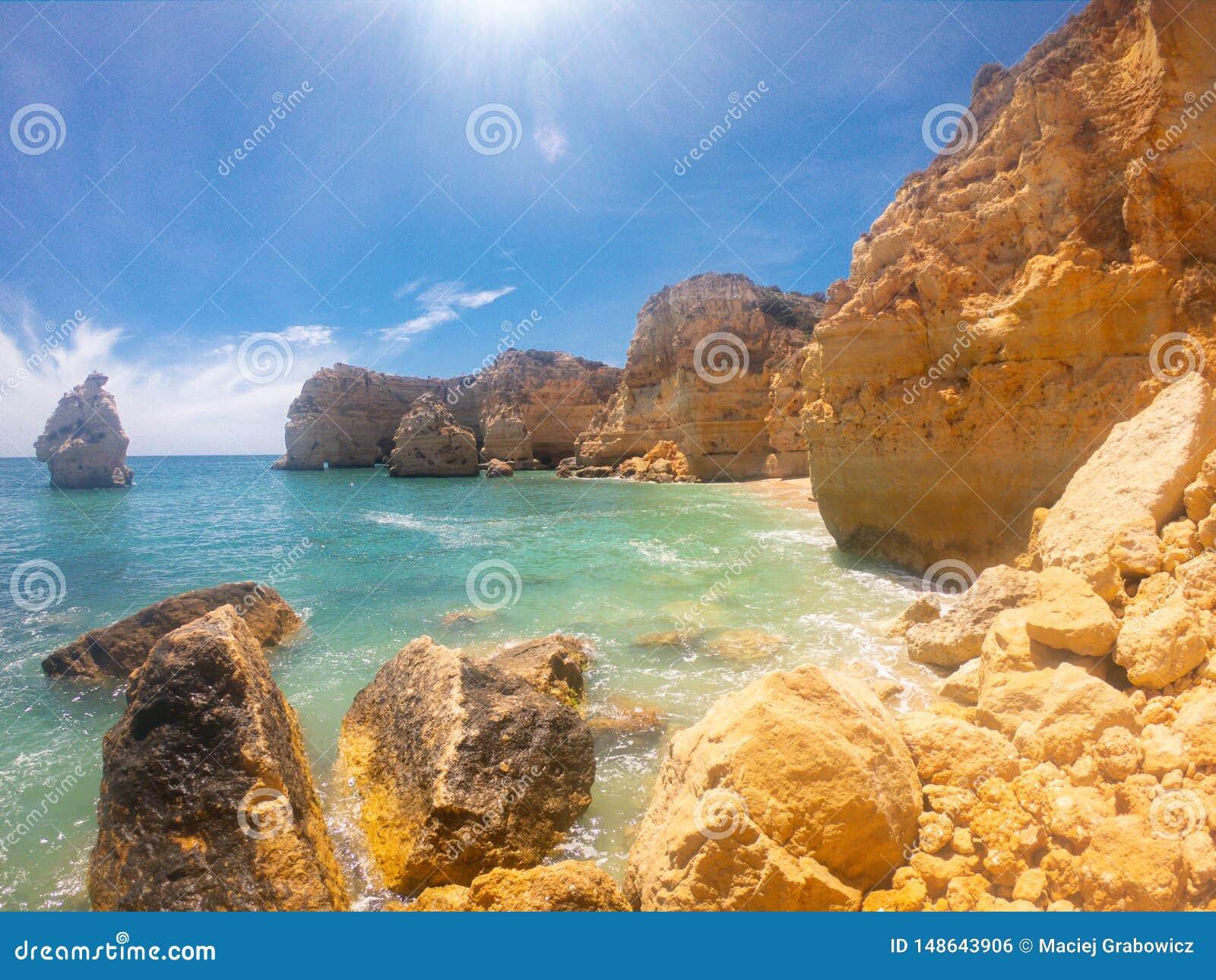 Praya de Marinha most beautiful beach in Algarve, Portugal. Cliffs on Coast of Atlantic ocean against blue sky