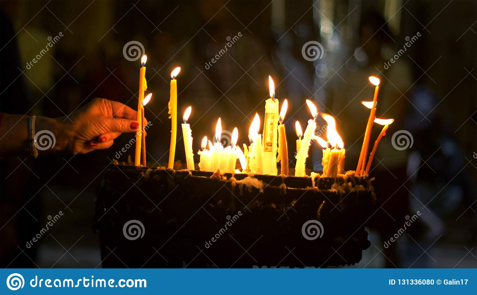 Close up of prayers hands lighting candles in the Holy Sepulchre Church in Jerusalem