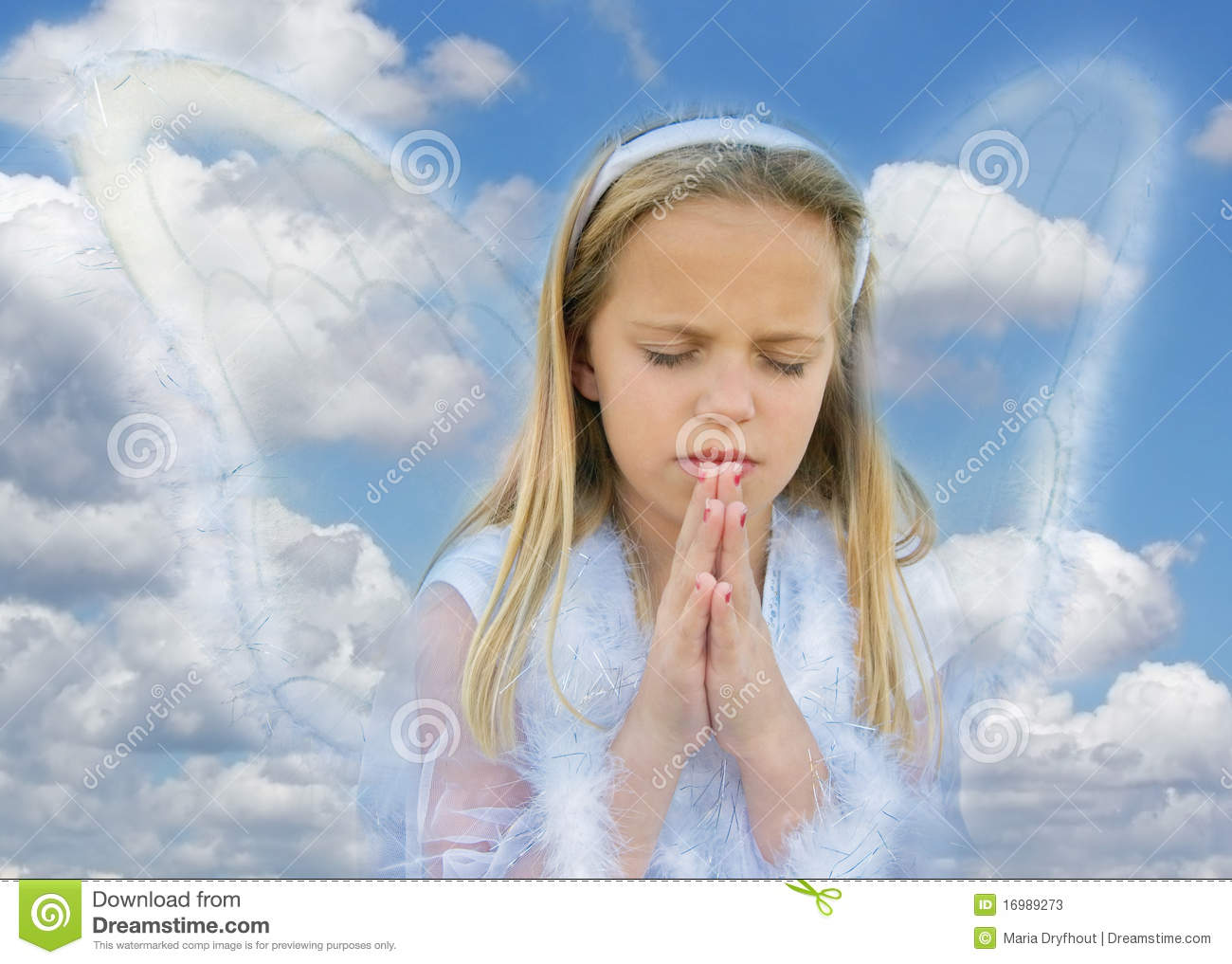 Young girl in praying pose with angel wings.