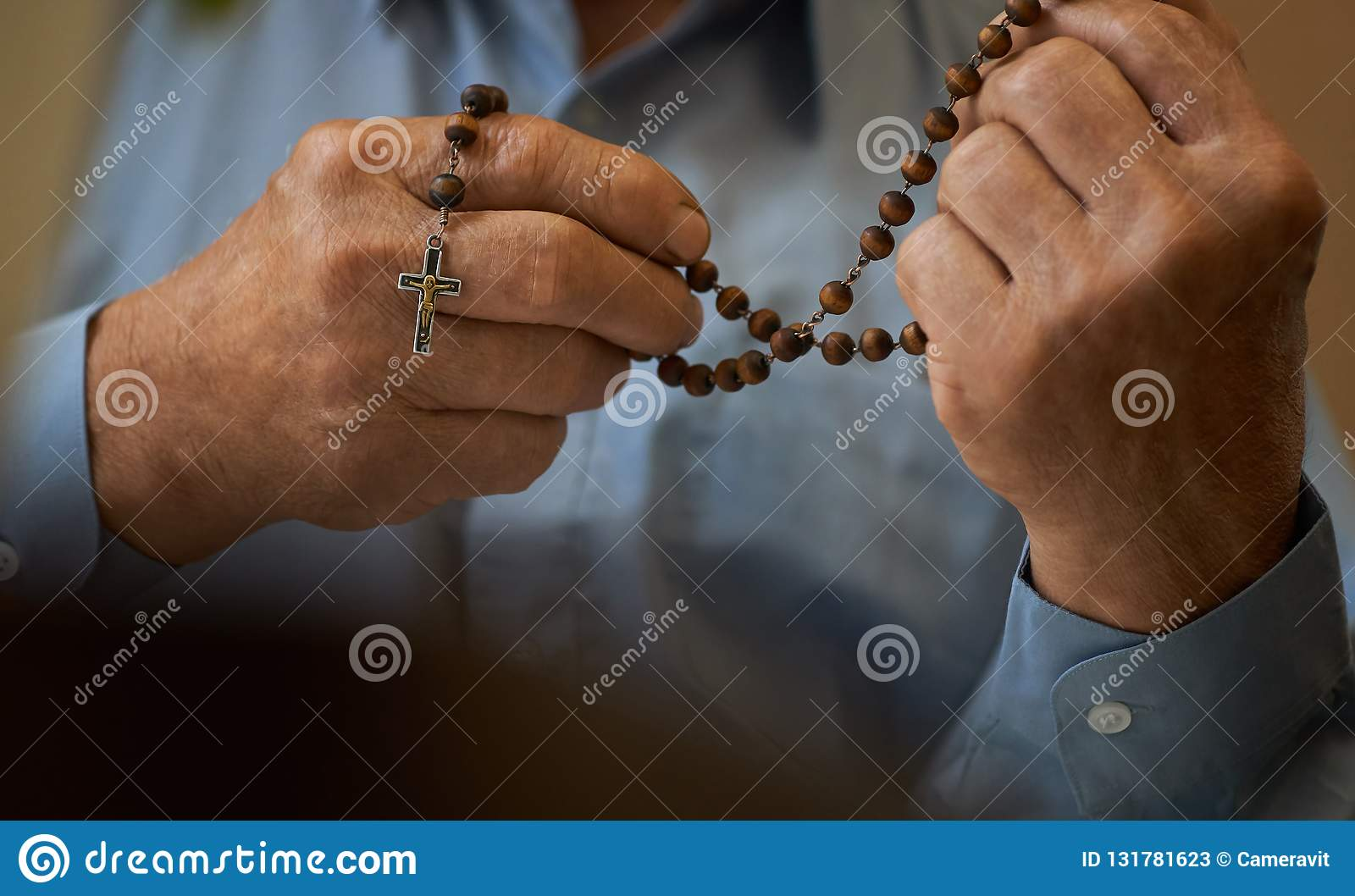 283031947 Royalty-Free Stock Photo. Praying hands of an old man holding rosary beads.