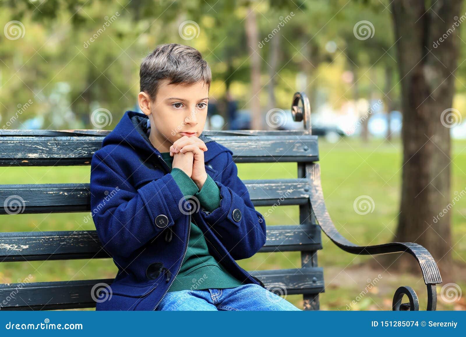 Praying little boy sitting on bench in park