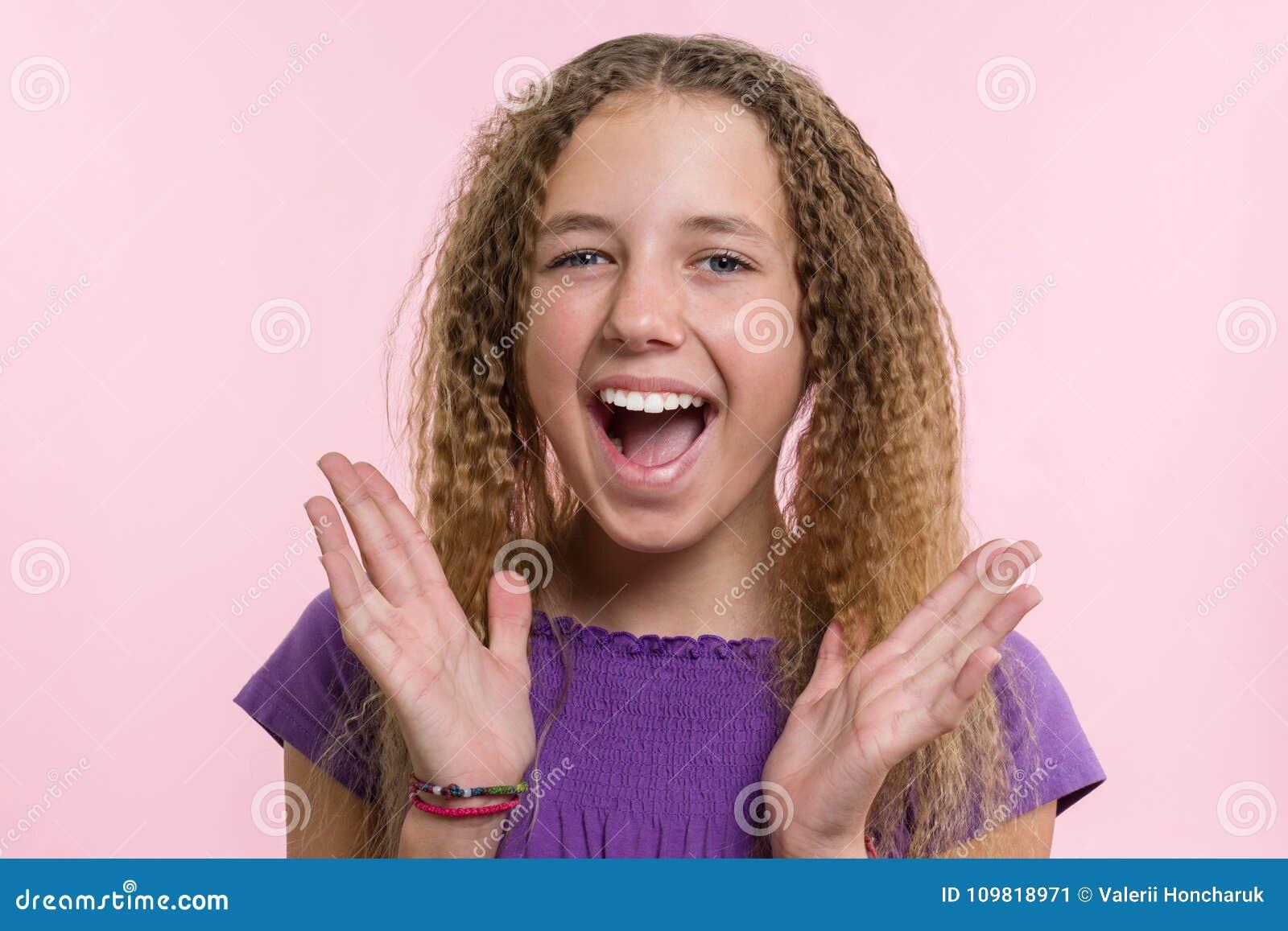 Prazer, felicidade, alegria, vitória, sucesso e sorte Menina adolescente em um fundo cor-de-rosa Expressões faciais e conceito da