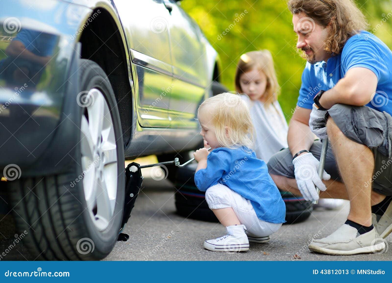 p re de aide de petite fille pour changer une roue de voiture. Black Bedroom Furniture Sets. Home Design Ideas