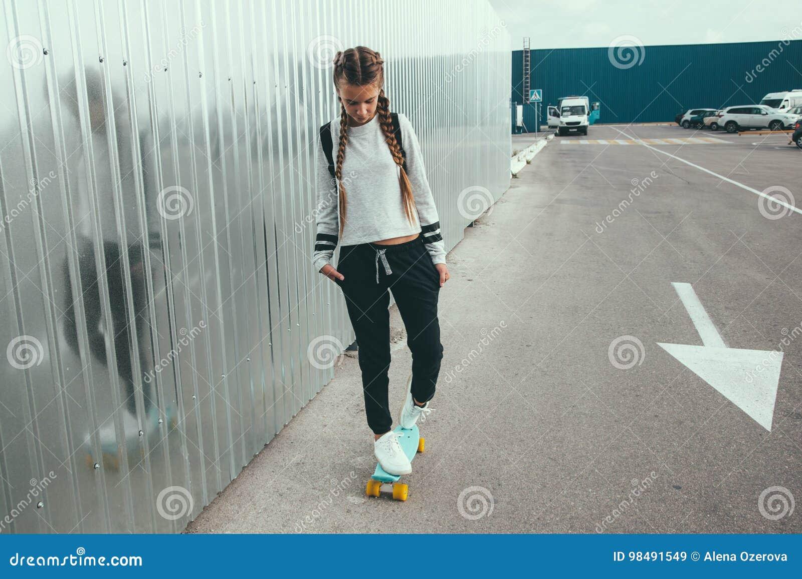 7e436da5d92 11-12 years old tween girl wearing fashion sportswear rollerskating on  skateboard in the city street