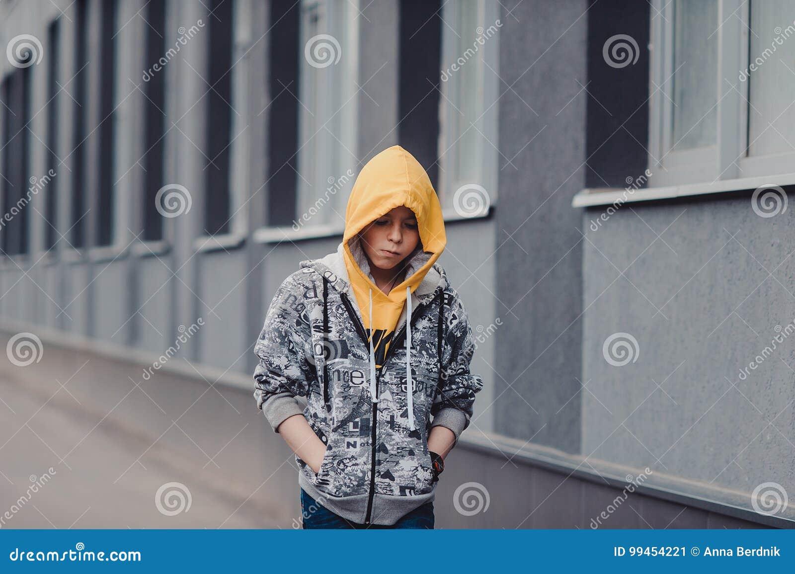 Pre-tonårig pojke på en gata i en storstad bredvid ett höghus bara