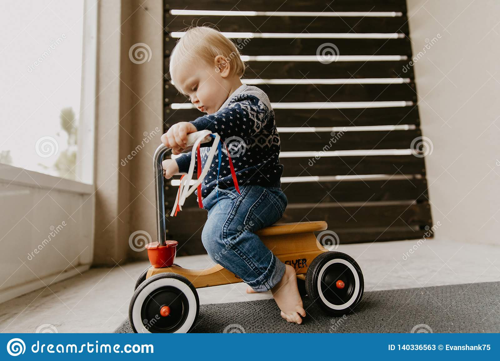 Precious Adorable Cute Little Blonde Baby Toddler Boy Kid Playing Outside on Wooden Toy Bicycle Scooter Mobile Smiling at the Came