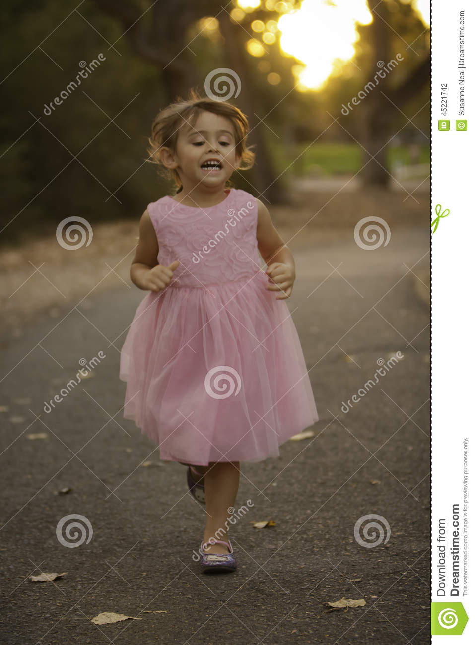 Pretty, 3-1/2 year old girl wearing a pastel pink fancy dress, running on a  path at a park. Girl has brown hair pulled back into a braid. She is  smiling.