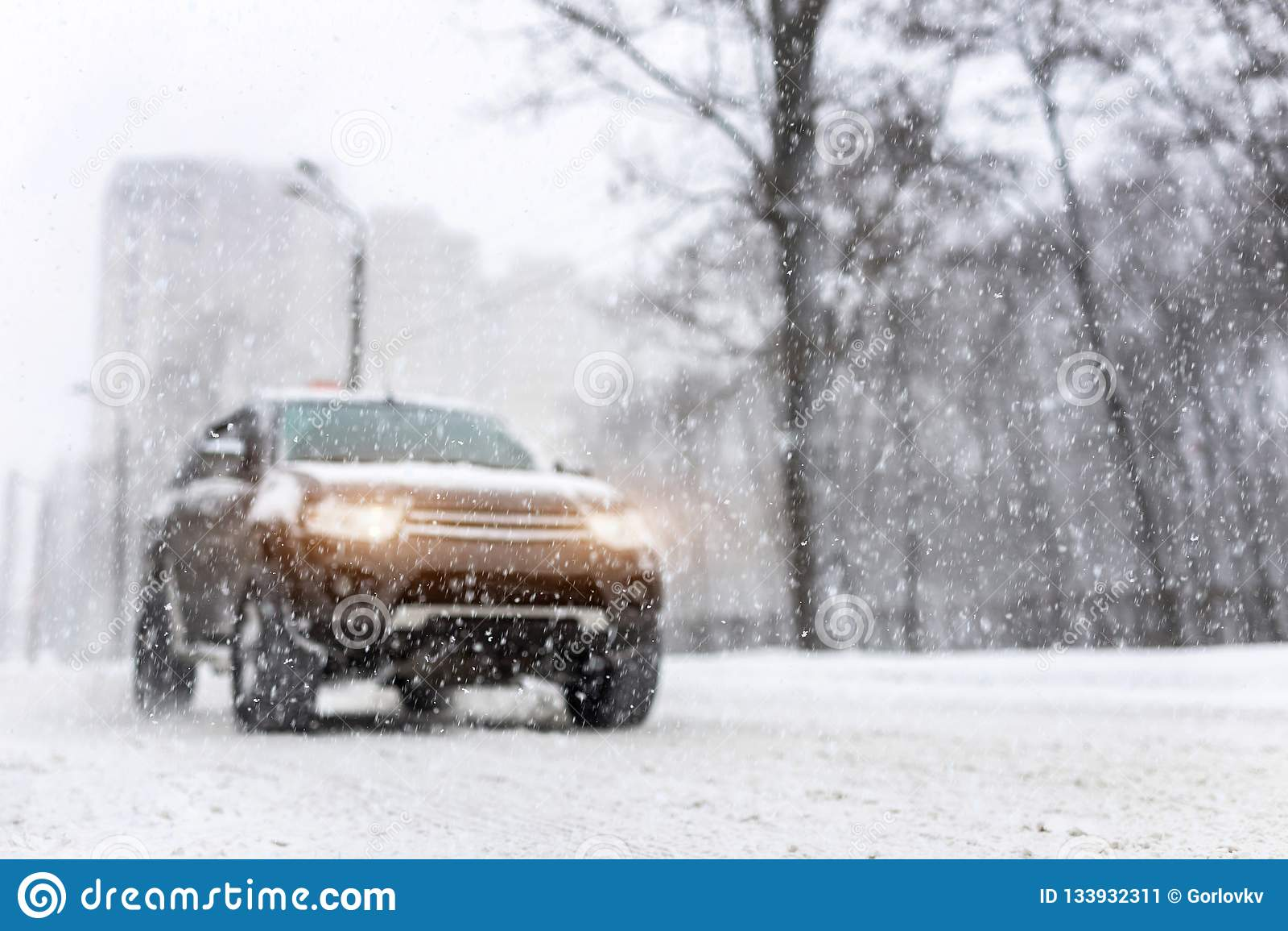 Precipitazioni nevose pesanti ed automobile awd vaga di SUV sulla strada veicolo 4wd sulla via della città all inverno Concetto s
