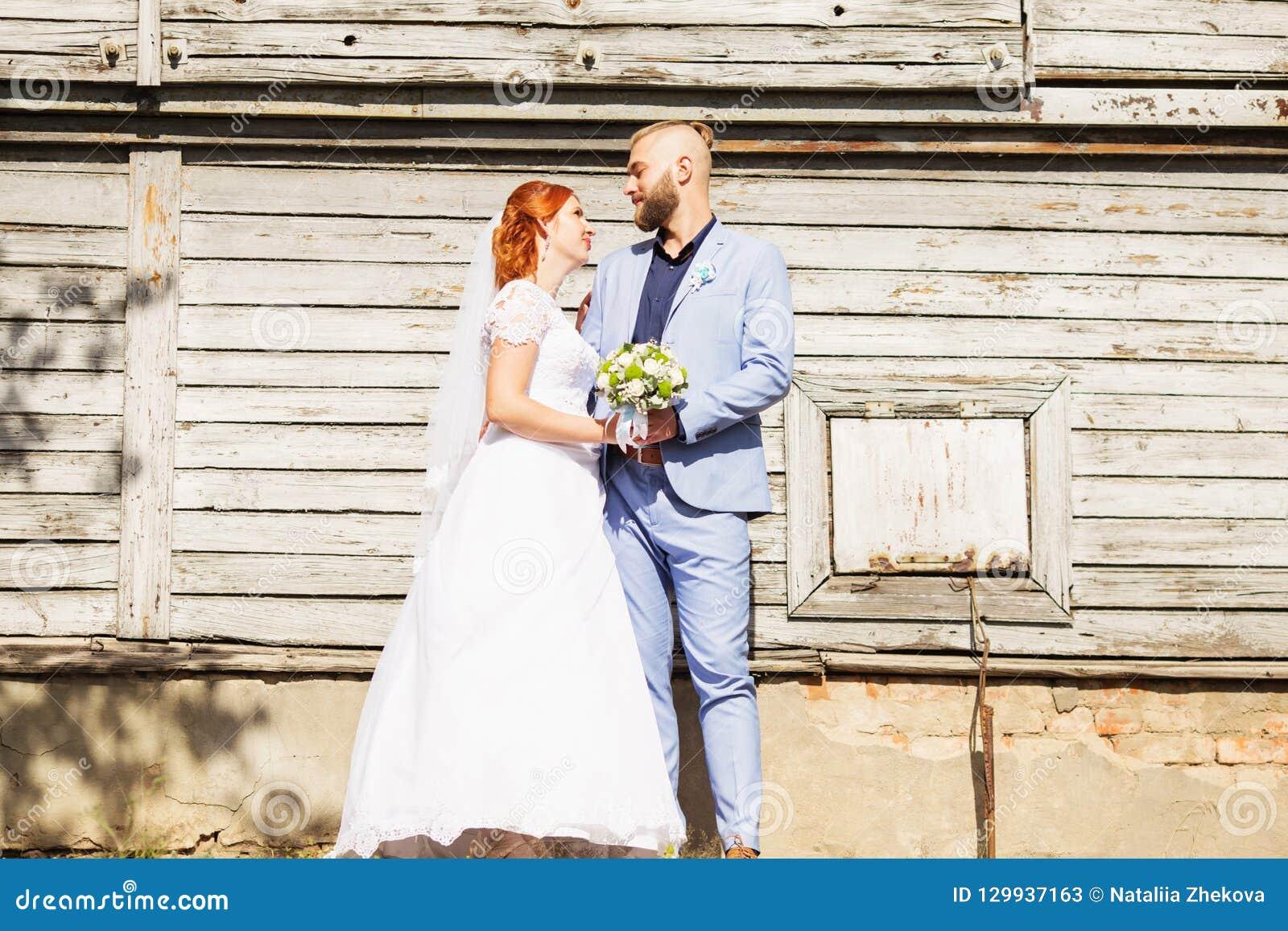 Precis gifta älska hipsterpar i bröllopsklänning- och dräktpos.