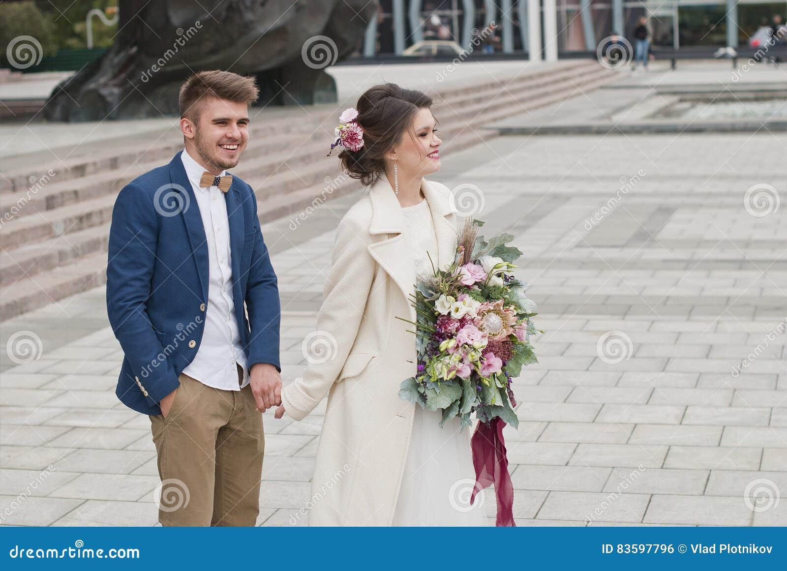 Precis gifta älska par i bröllopsklänning och dräkt Lycklig brud och  brudgum som går att köra 74a3c08ae1622