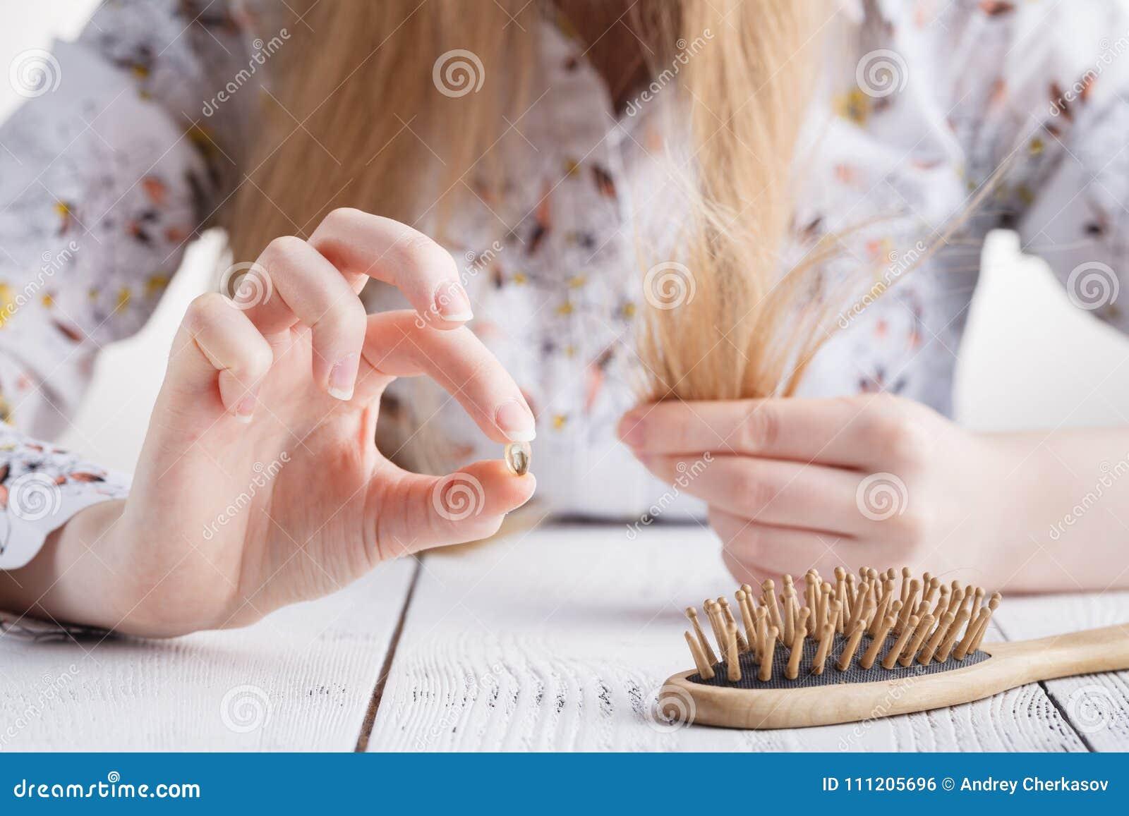 Precise mais vitaminas, mulher com problemas do cabelo, cabelo perdido no pente