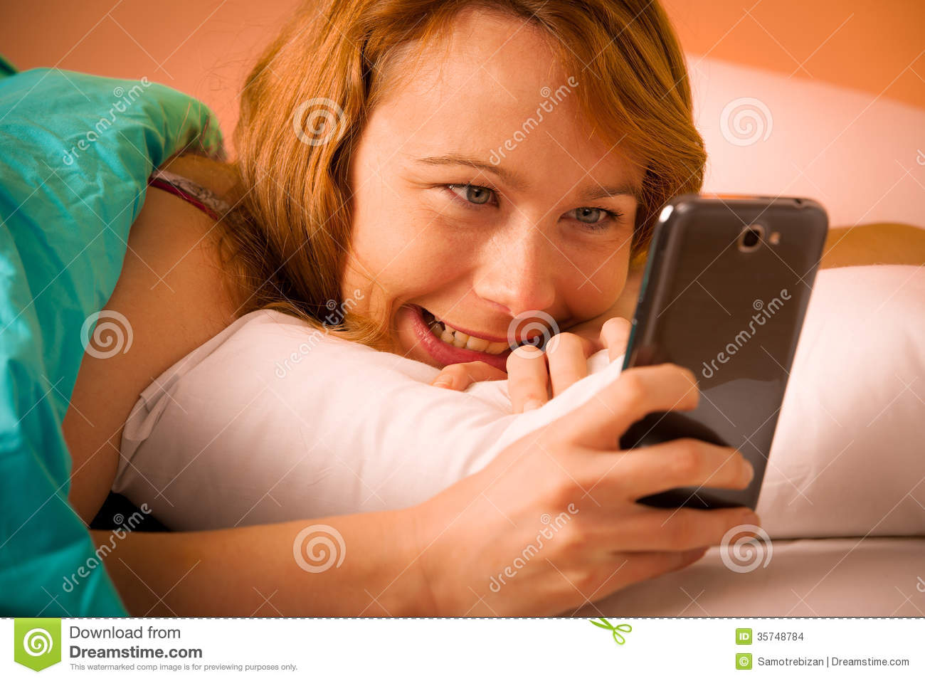 Preety woman reading a sms on cell phone in bed stock for Cell phone bed