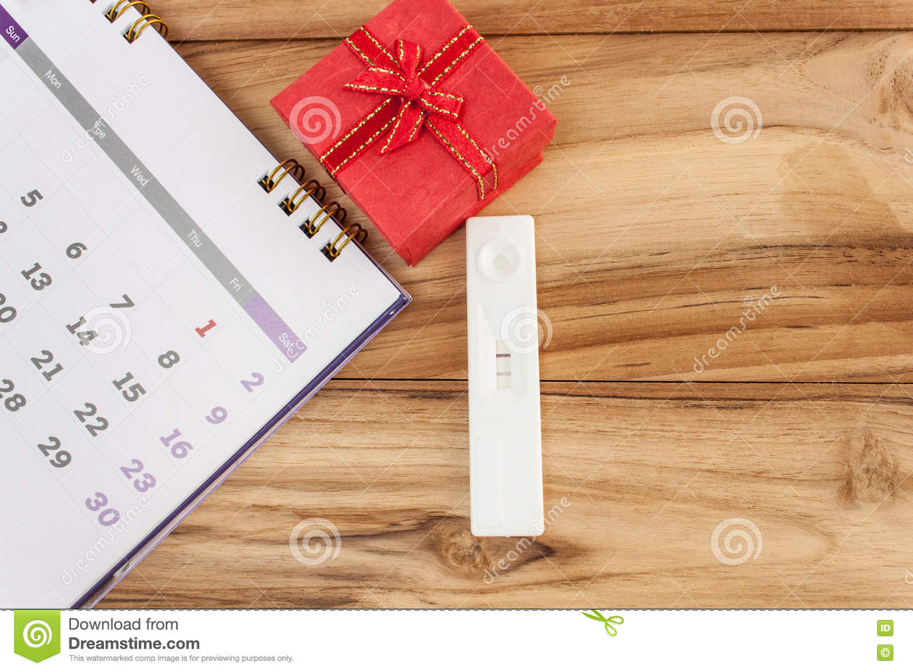 pregnancy and calendar red gift boxes on a wooden table