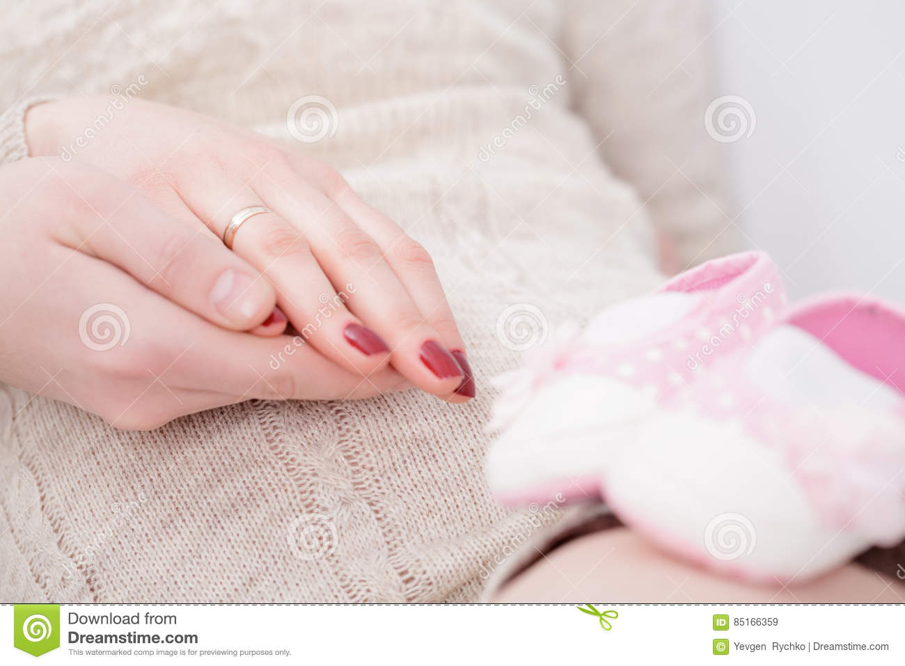 Pregnancy - Hands Of Mother And Father. Pink Booties In The Fo Stock ...