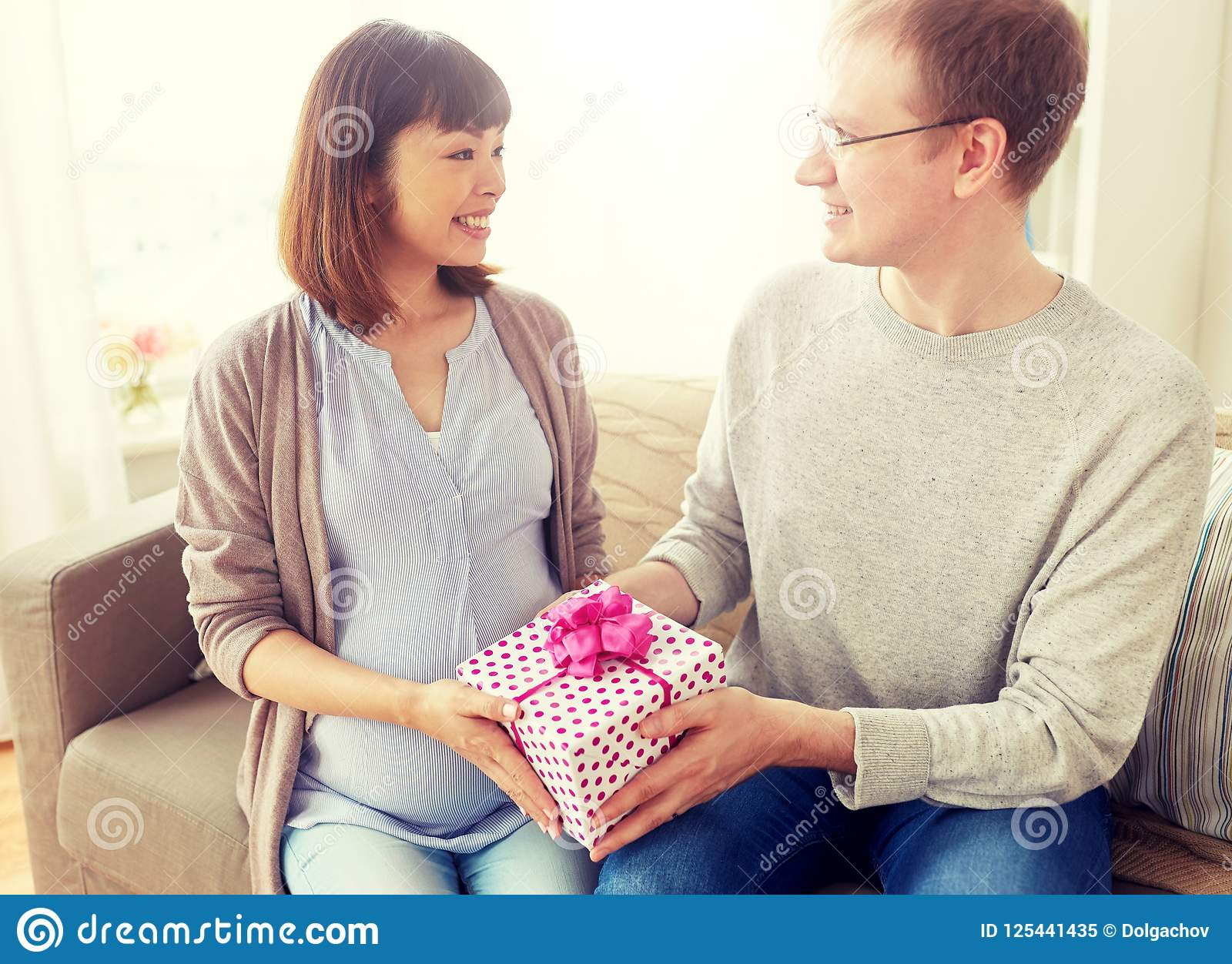 Husband Giving Birthday Present To Pregnant Wife Stock Image