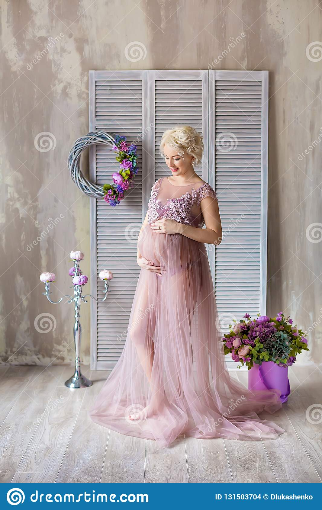 Pregnancy, motherhood and happy future mother concept - pregnant woman in airy violet dress with bouquet flowers against colorful