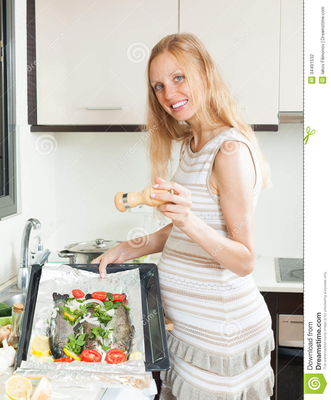 Pregnancy woman cooking trout fish stock photography for Fish dream meaning pregnancy