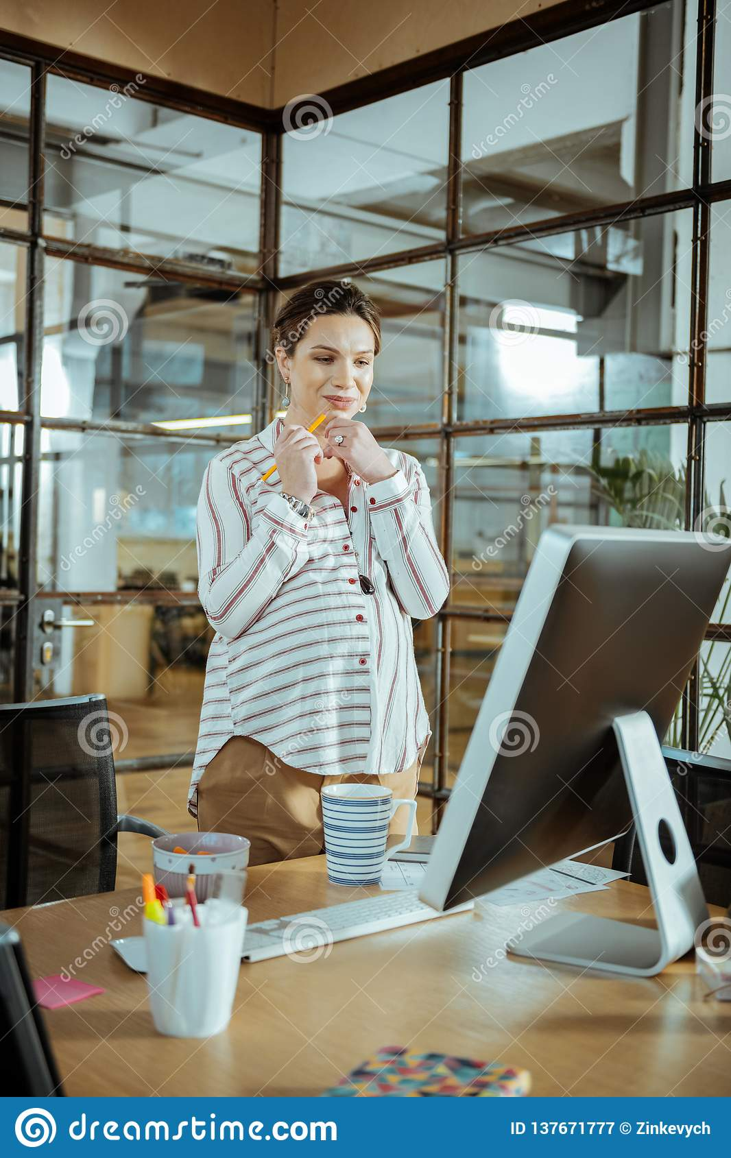 Young pregnant businesswoman working in modern office
