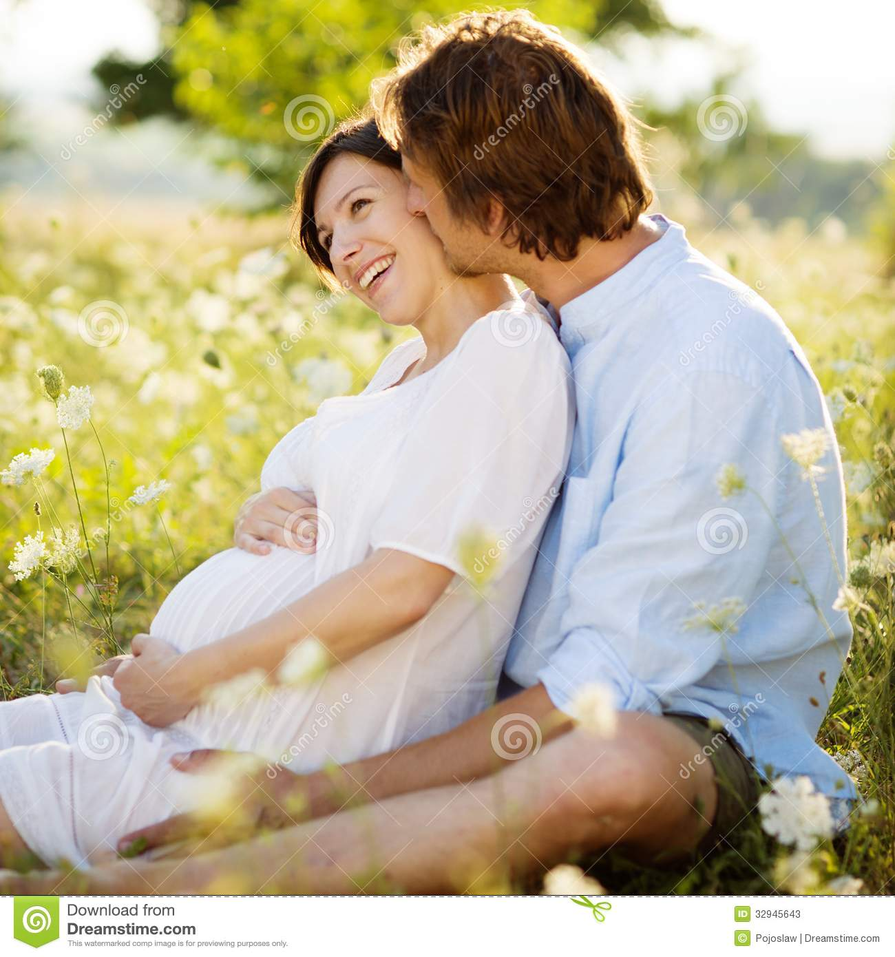 Young Happy Beautiful Family Playing Together On The Beach: Pregnant Couple Stock Photos